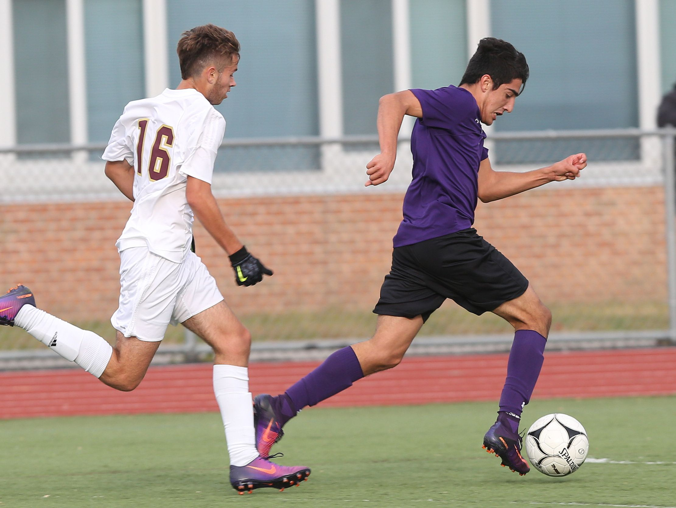 New Rochelle's Cristian Valencia (7) breaks away from Arlington's (16) as he shoots his second goal of the first half during the boys soccer Section 1 Class AA championship game at Lakeland High School in Shrub Oak High School Oct. 29, 2016. New Rochelle won the game 3-0.