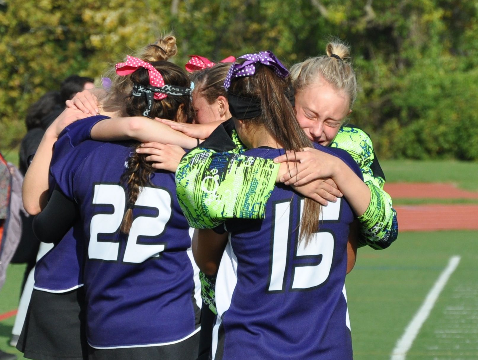Goalie Haley Martinsen (in green) and other members of the John Jay field hockey team try to console each other after their semifinal loss to Rye.