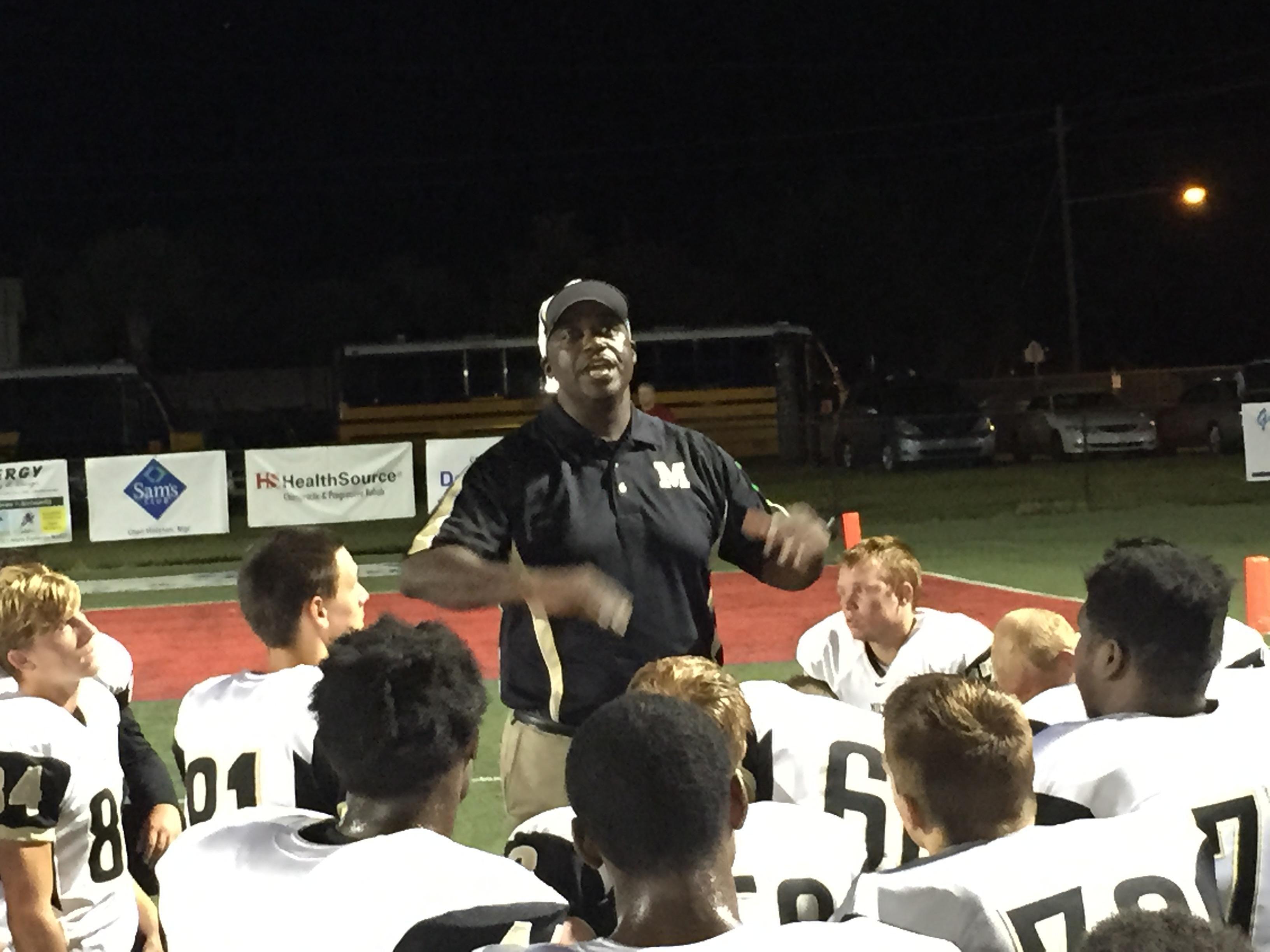 Milton football coach Chafan Marsh talks with his team following Friday night's 38-7 victory against Fort Walton Beach High at Steve Riggs Stadium in Fort Walton Beach.