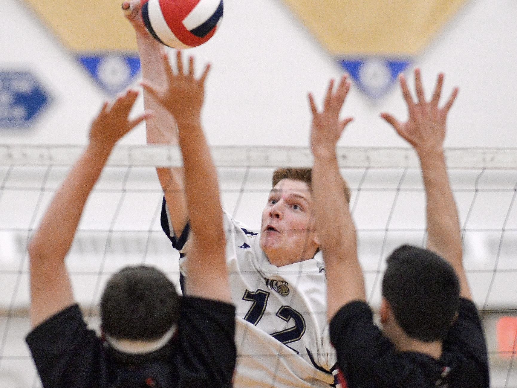 Webster's Justin Spiegel hits over the block of Hilton's Joe Hoover and Bryce Thompson.