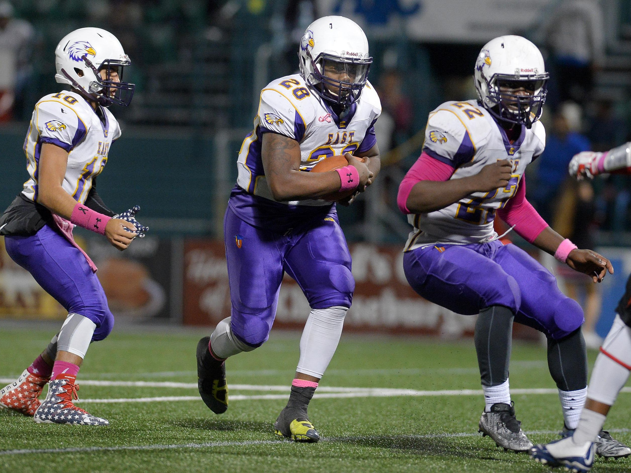 East's Deljon Johnson, center, carries the ball for a two-point conversion.