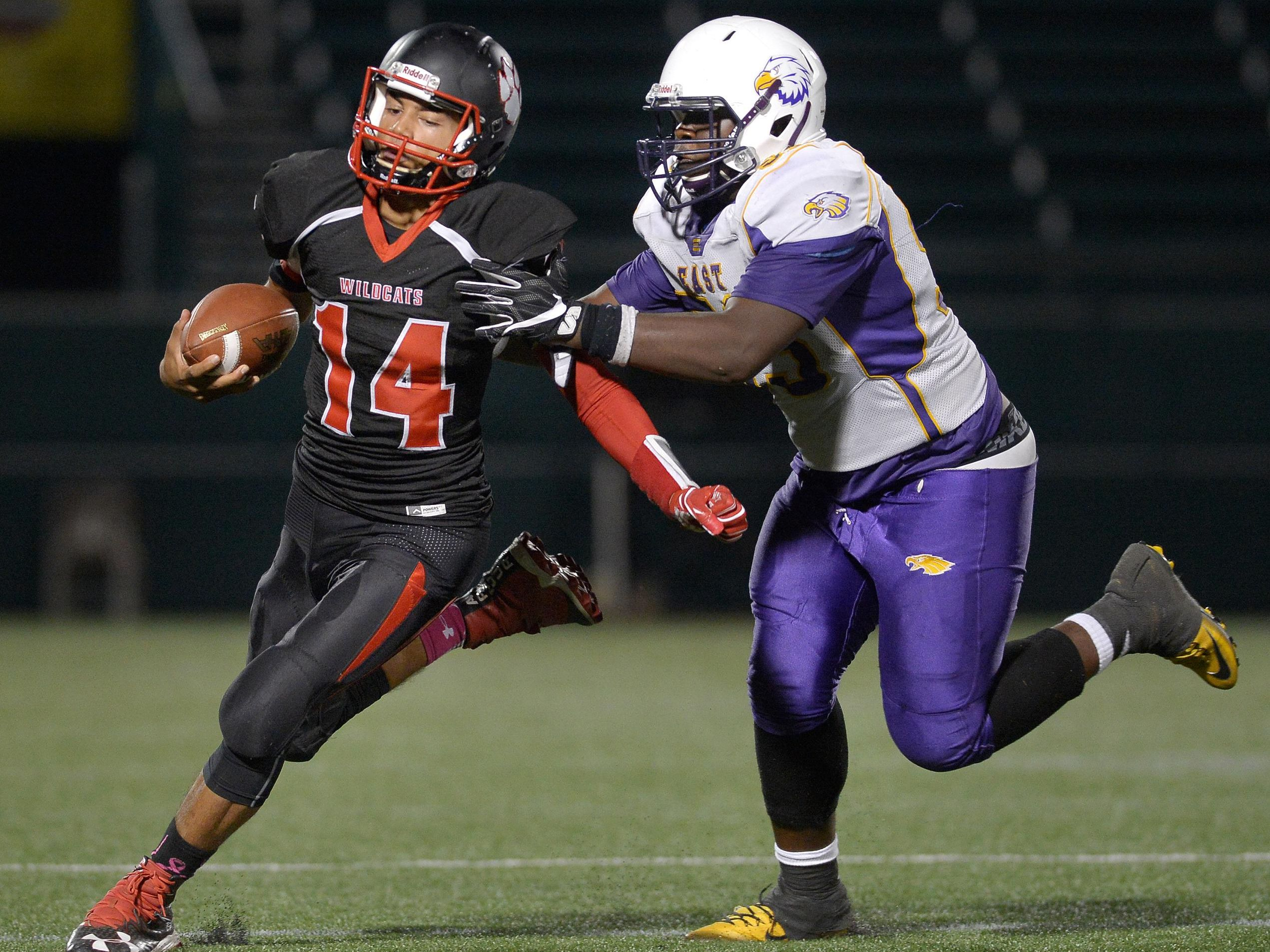 Wilson quarterback James Cotton, left, is pursued by East's Charles Brown.
