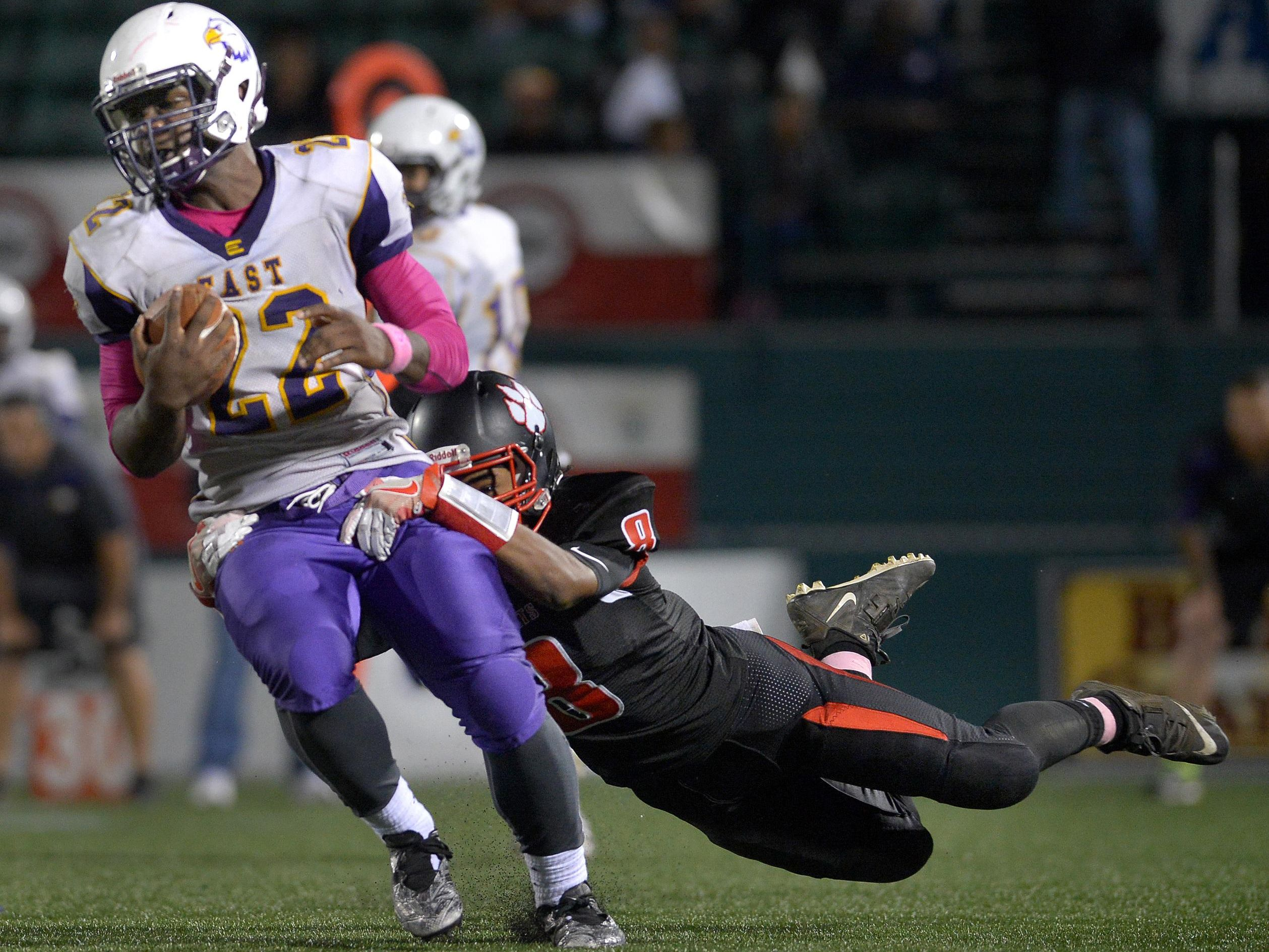 East's Cipher Campbell-Bollar is tackled for a loss by Wilson's Dallas Cooper.