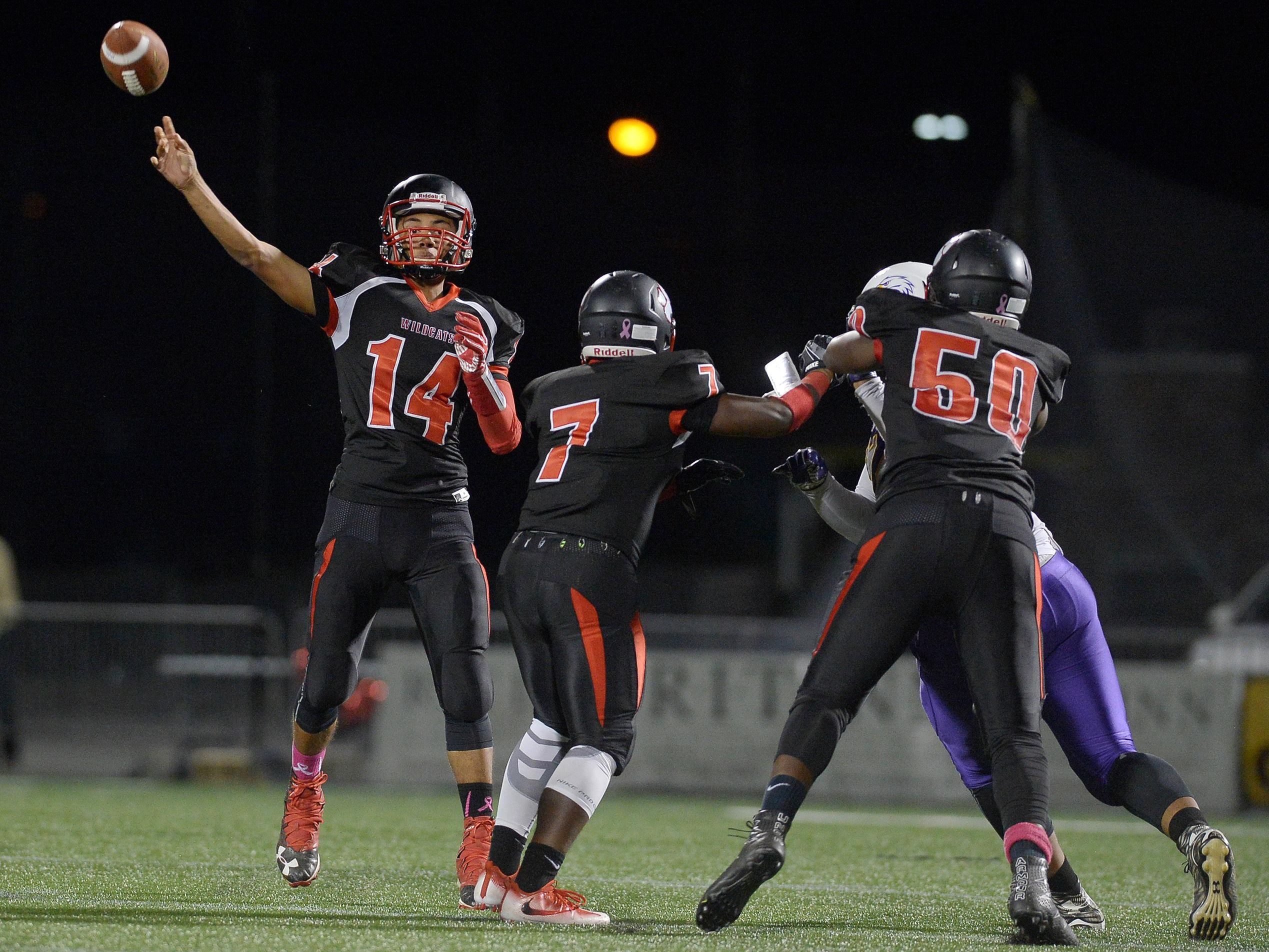 Wilson quarterback James Cotton throws a long pass from the pocket.