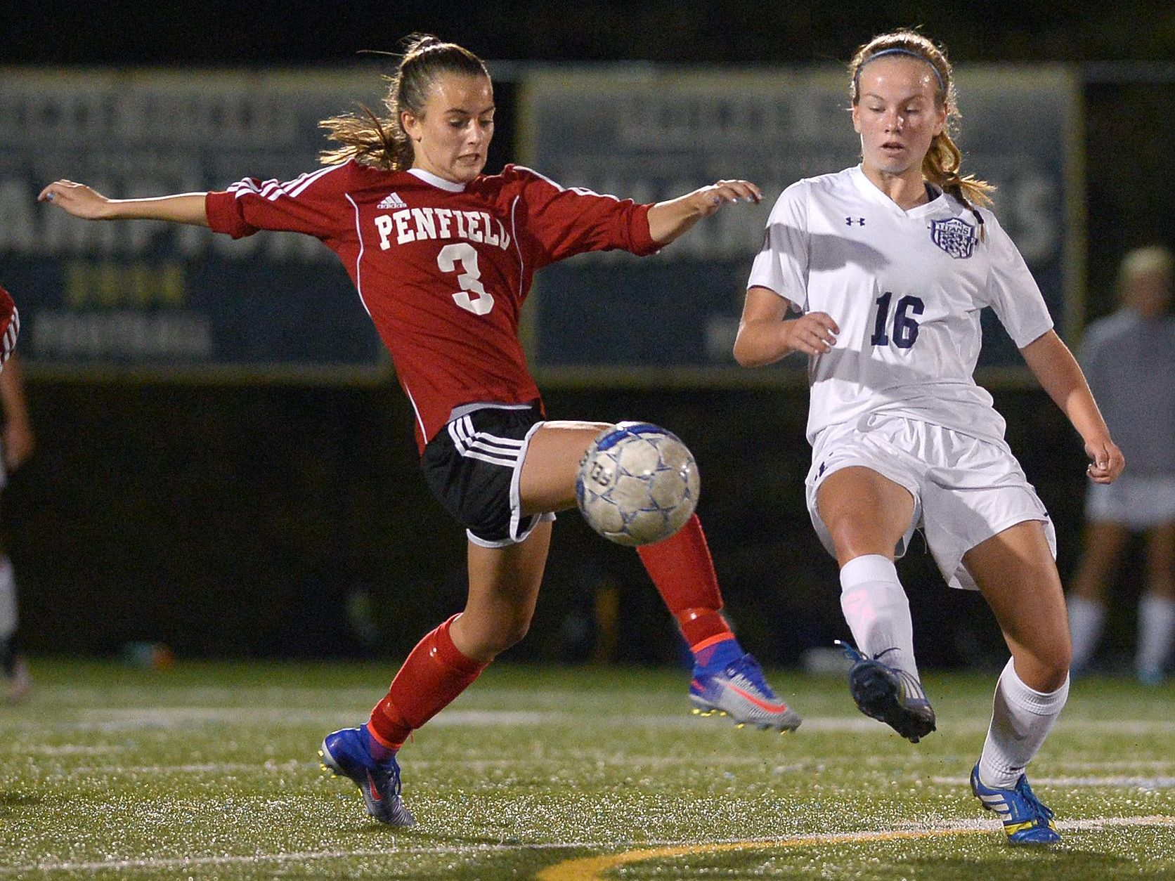 Webster Thomas' Sarah Riedel, right, clears the ball past Penfield's Grace Murphy.