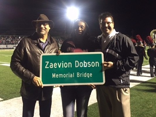 Former state Rep. Joe Armstrong, Zenobia Dobson and state Rep. Eddie Smith show the new Zaevion Dobson Memorial Bridge sign during halftime of the Fulton High School football game (Photo: Chierstin Susel, WBIR)