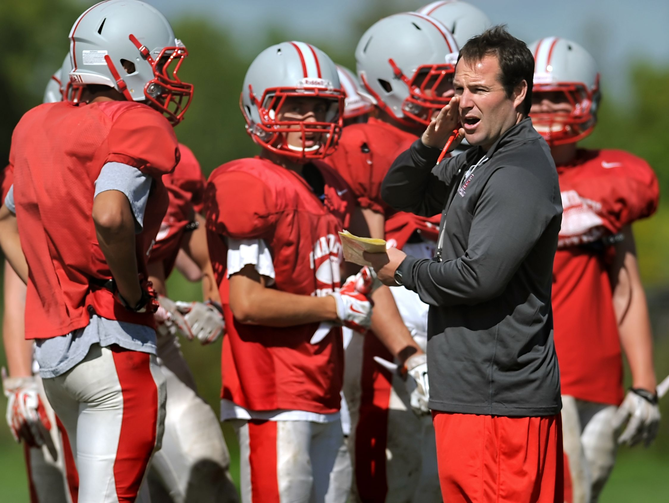 Canandaigua head coach Jeff Welch, right, calls to the sideline as he runs preseason football practice at Canandaigua Academy on Thursday, August 28, 2014.