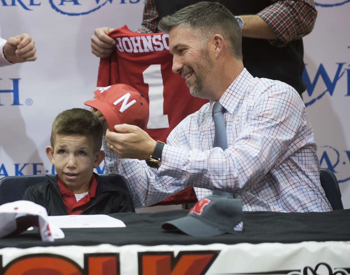Jack Johnson gets help putting on his Nebraska hat from his dad during a signing day ceremony (Photo: Jack Wragge, Norfolk Daily News via Associated Press)