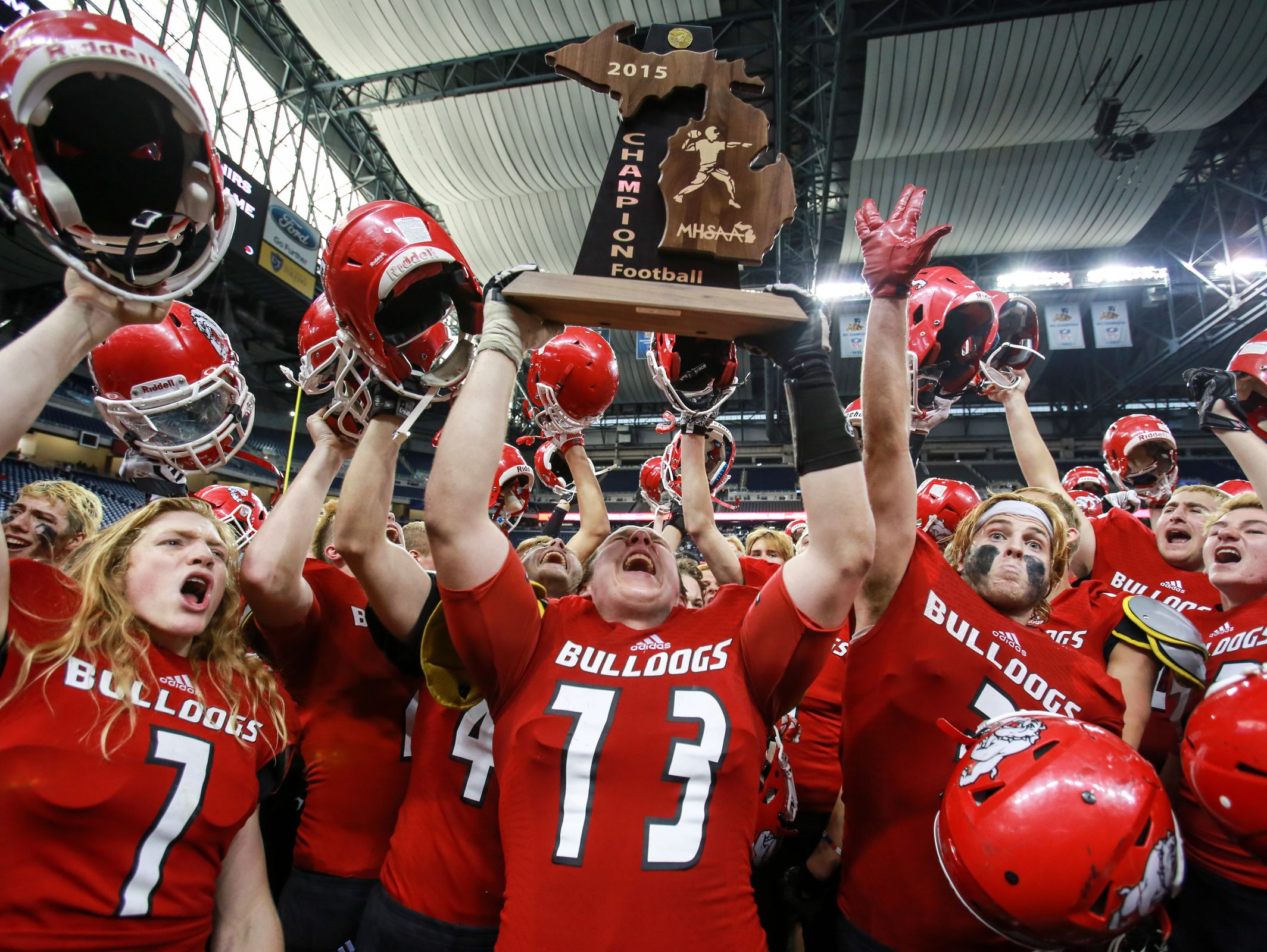 Romeo's Christopher Zanke lifts the MHSAA Football Champion trophy in the air surrounded by his teammates, after defeating Detroit Cass Tech in the Michigan High School Athletic Association football Division 1 finals at Ford Field in Detroit on Saturday, Nov. 28, 2015.