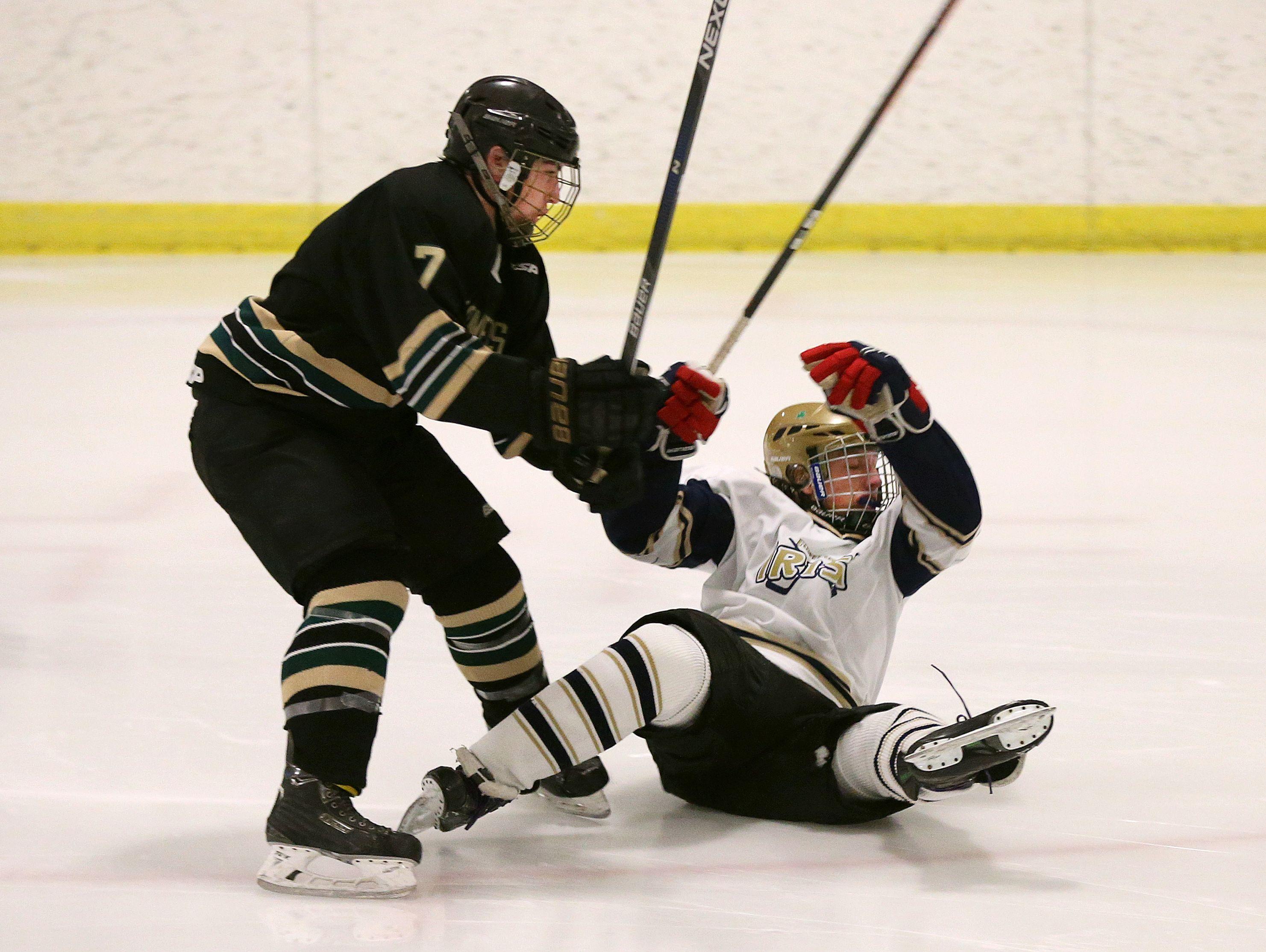 Batavia Notre Dame's Cameron Clark gets checked to the ice by Rush-Henrietta's Keegan White (7).