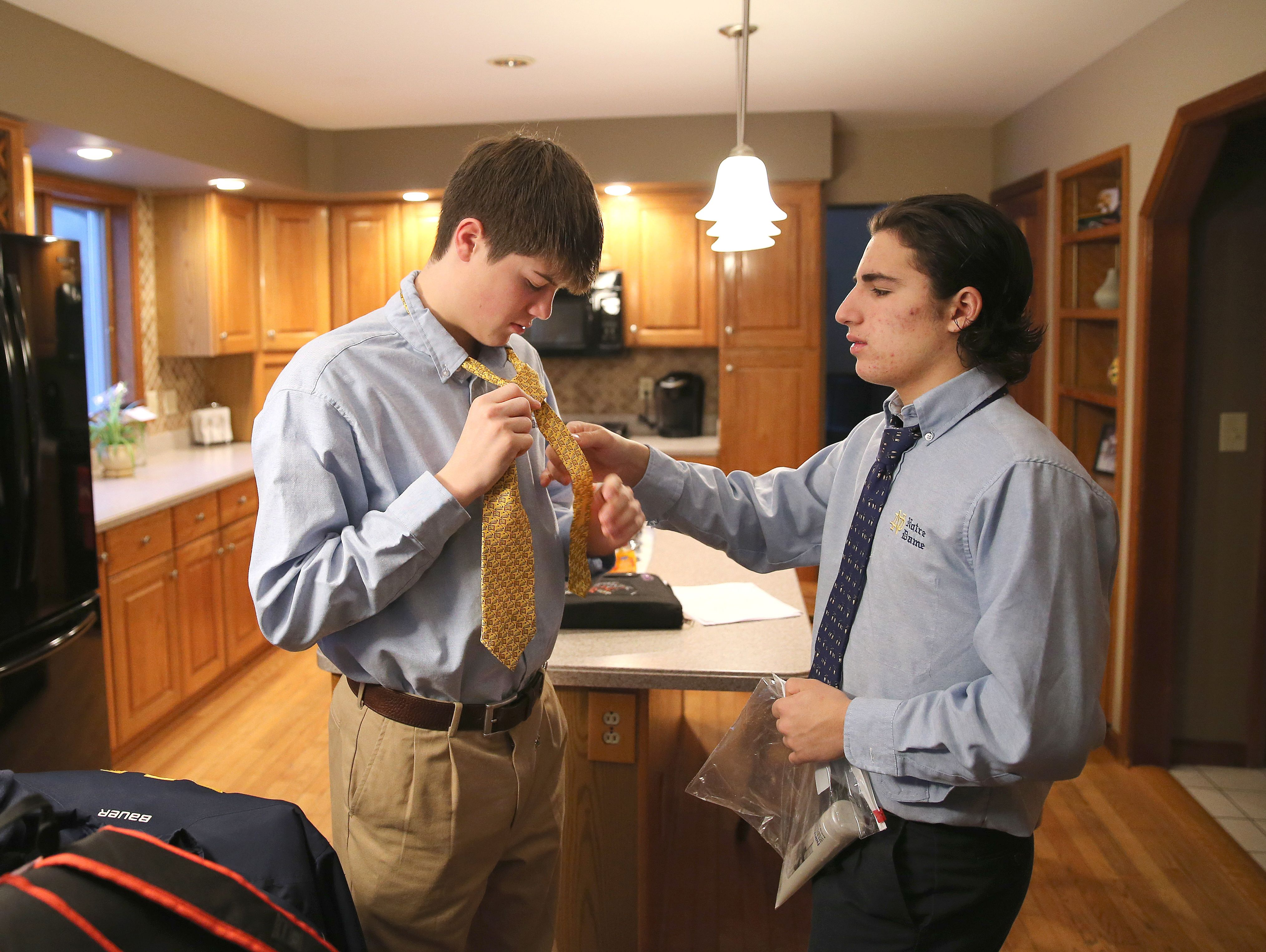 Batavia Notre Dame hockey players get dressed for school at the house of teammate Ethan Hutchins each morning after practice. Zachary Akin, left, gets some help with his tie from Michael Keeler.