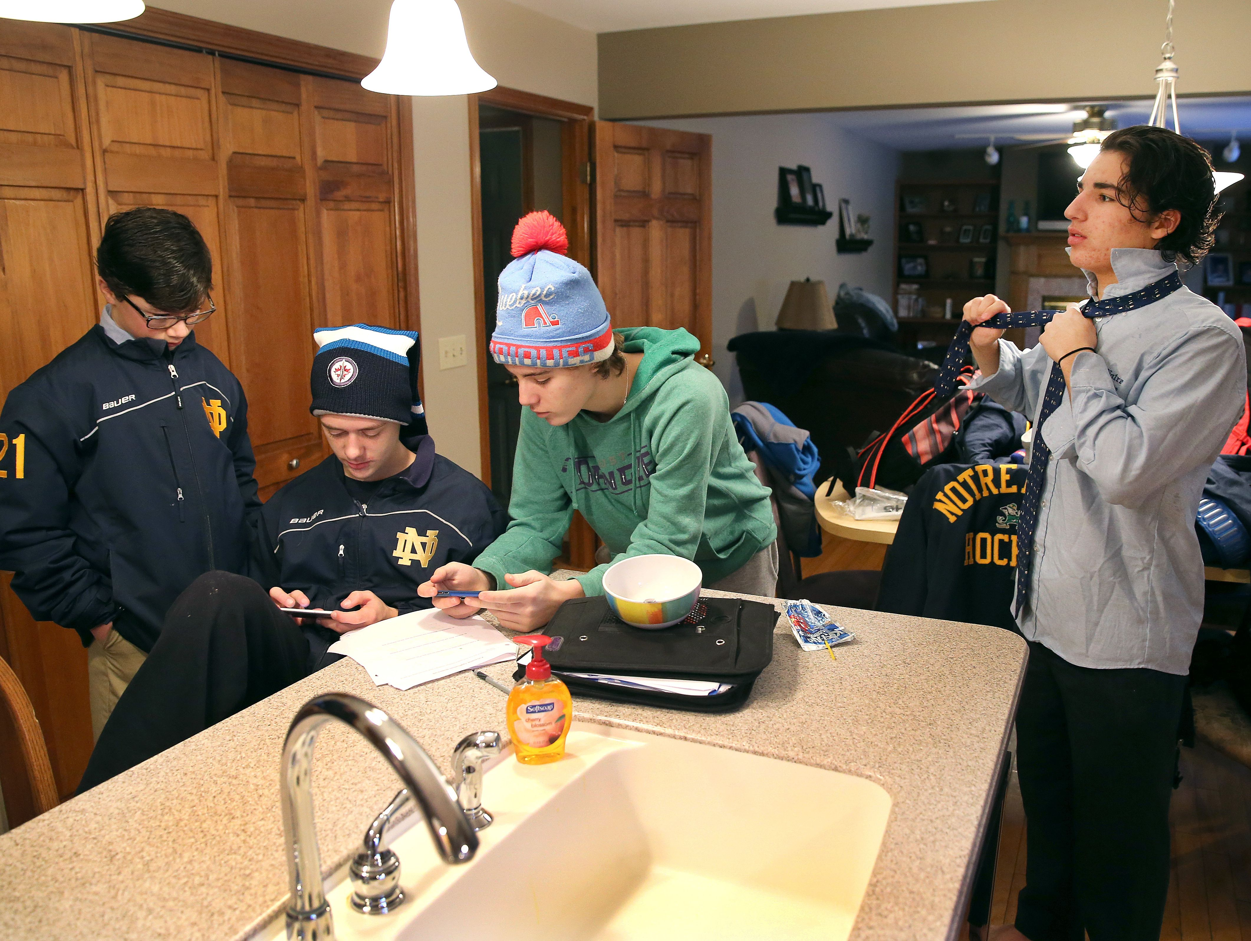 Batavia Notre Dame hockey players get ready for school after an early-morning practice.