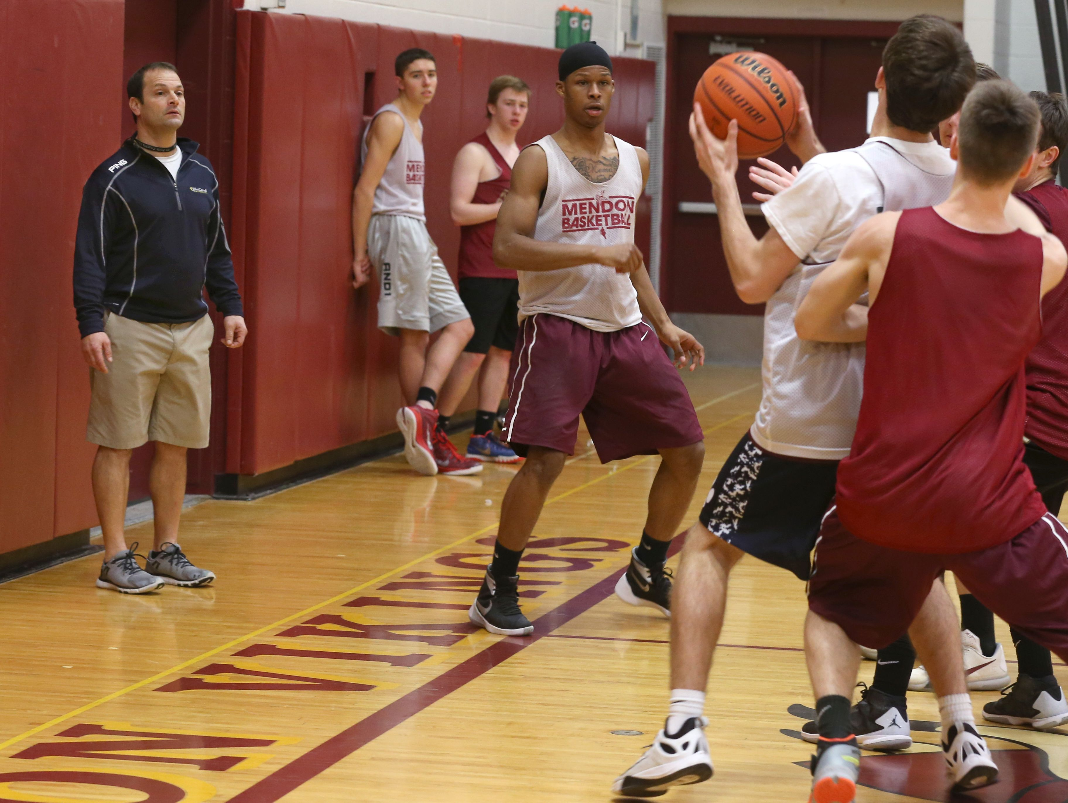 Jeff Amoroso, Pittsford Mendon boys varsity basketball assistant coach, watches from the sideline as his players run in-bounds drills during practice Tuesday at the high school.