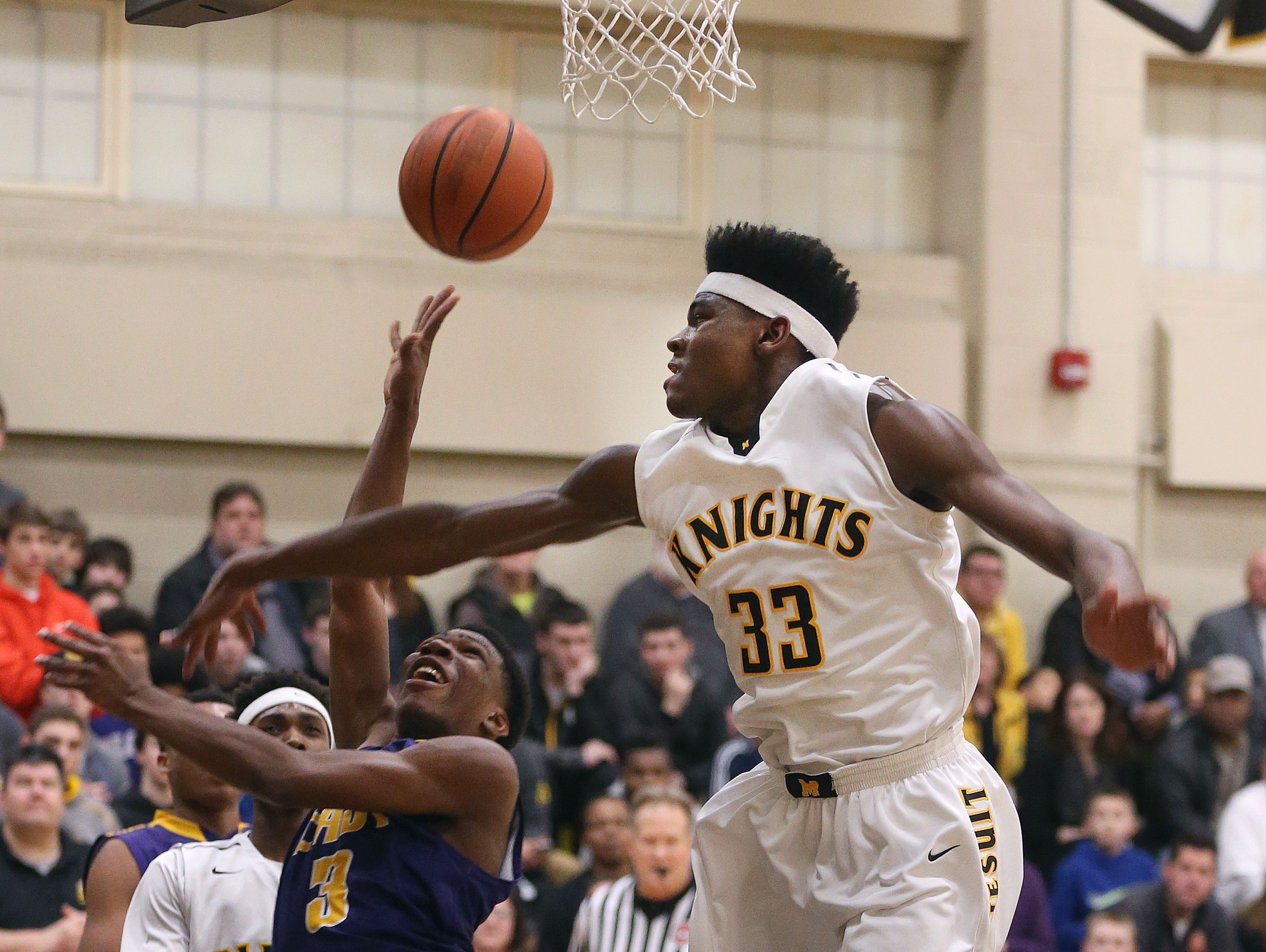 East's Zion Morrison (3) tries to shoot around the pressure by McQuaid's Isaiah Stewart (33) as the Knights went on to a 70-56 win.