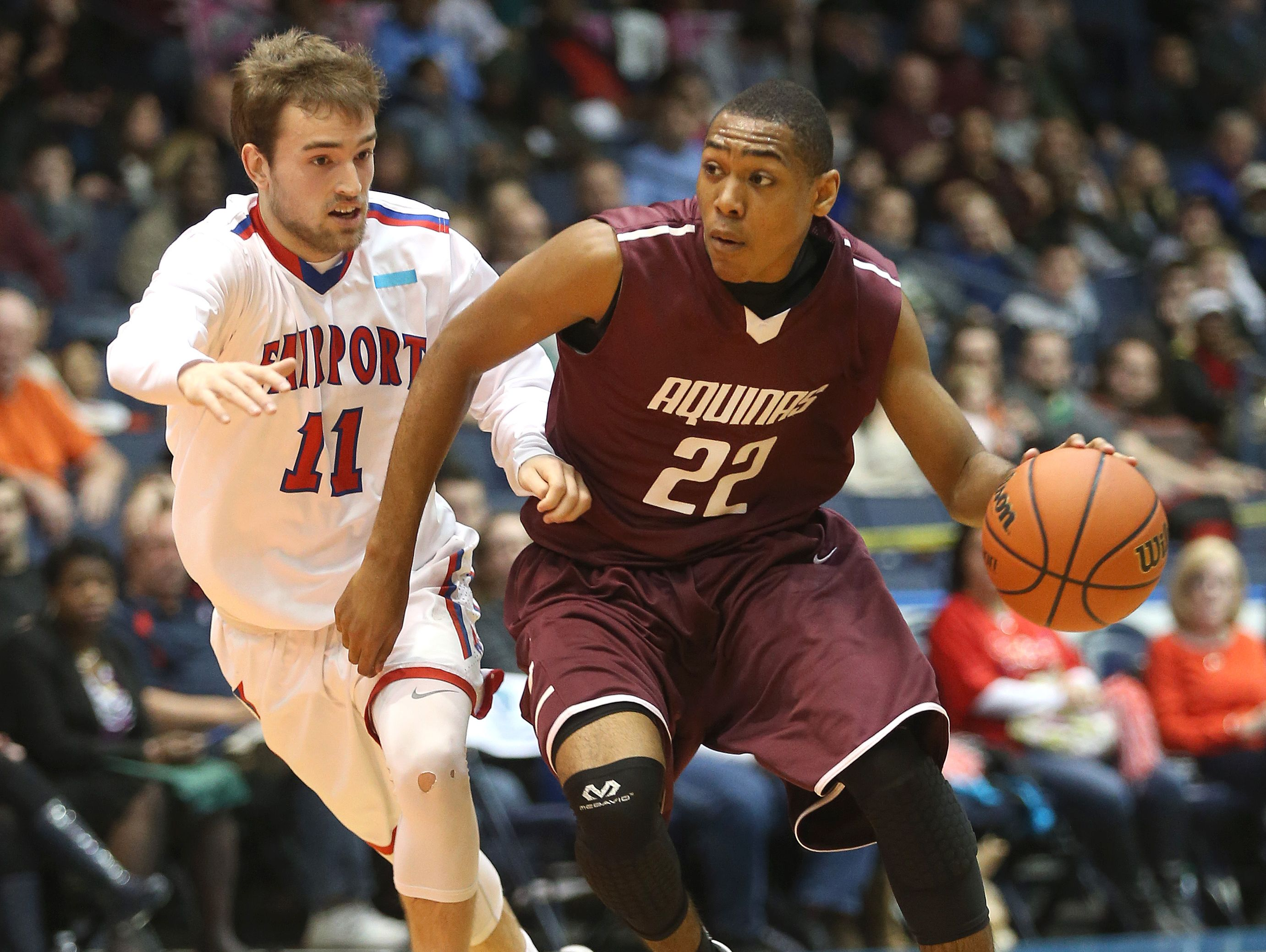Aquinas junior guard Jalen Pickett (22) is guarded by Fairport's Nick Lapp in the Section V Class A final.