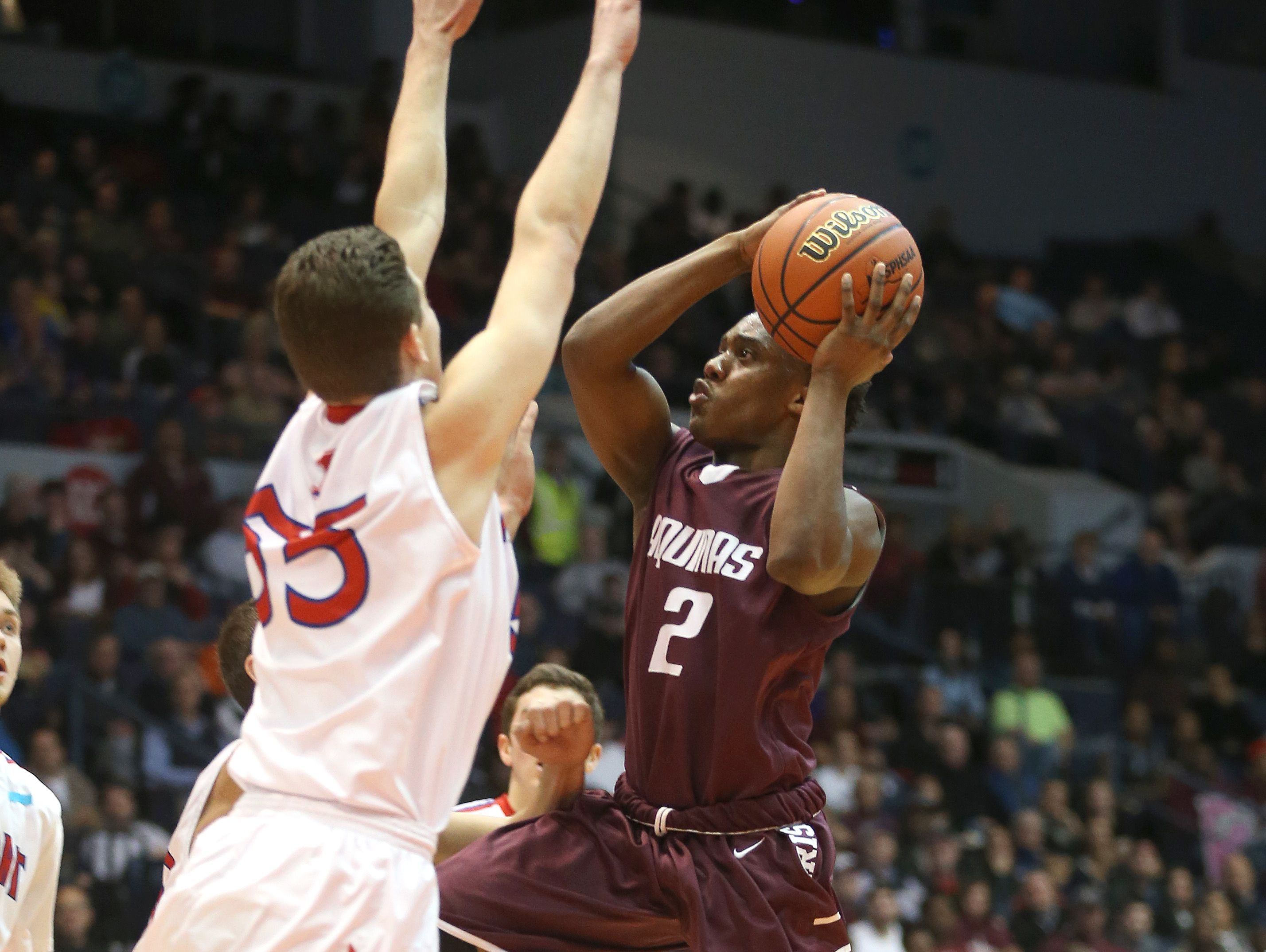 Aquinas's Earnest Edwards drives to the basket against Fairport's Cam Keeley (55). Edwards scored 23 in a 47-43 Aquinas win in the Class AA final.