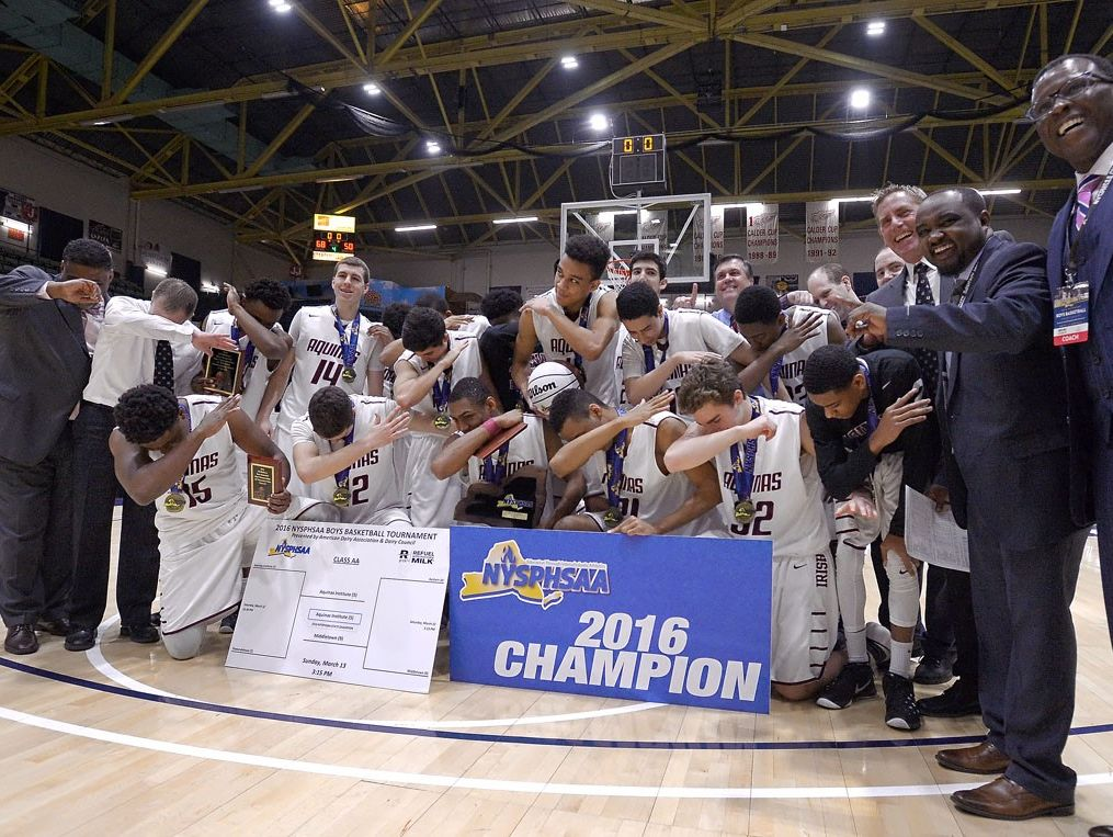 Aquinas players celebrate their Class AA state championship.
