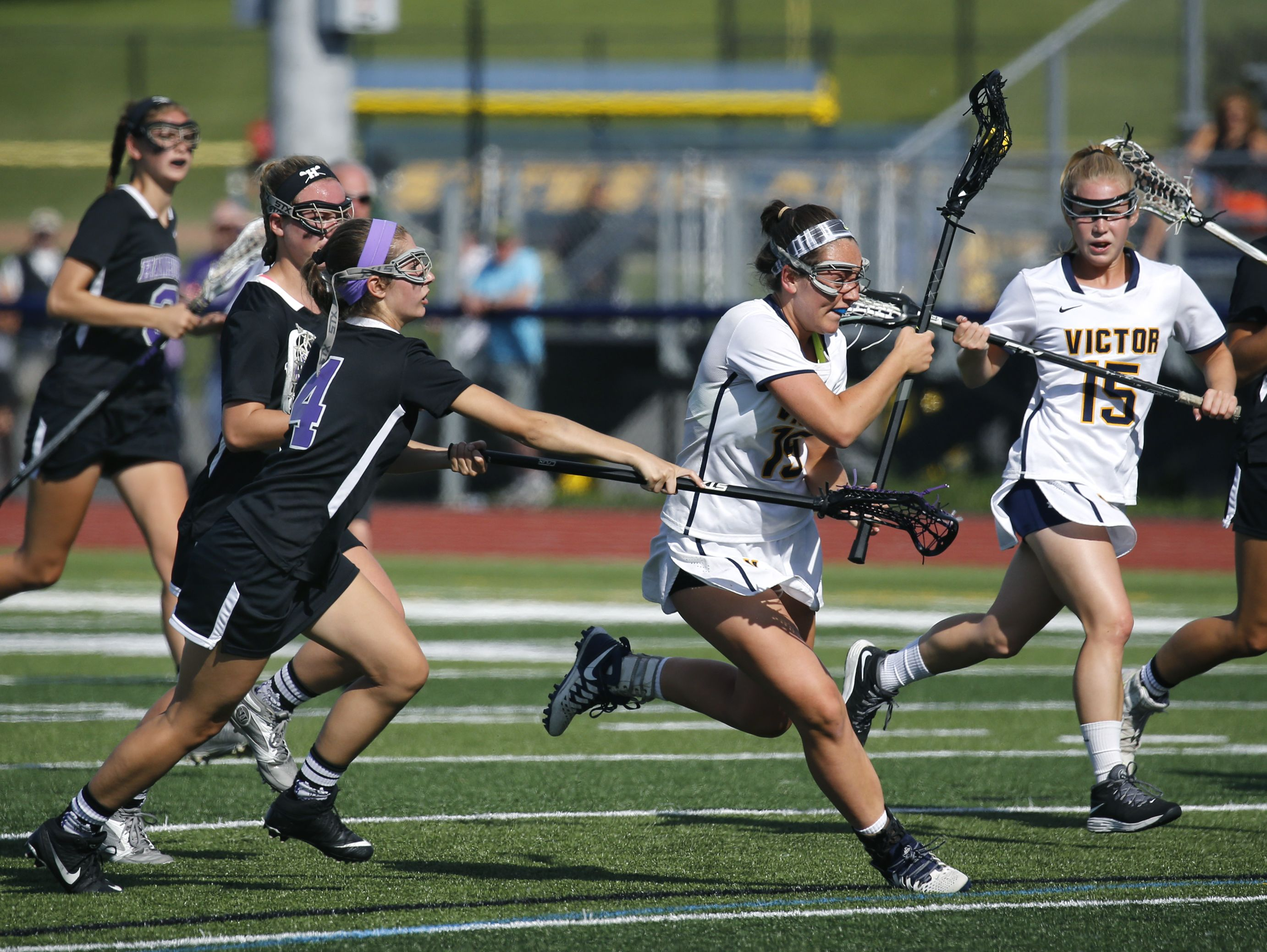 Victor's Bridget Flynn runs with the ball as Hamburg's Maddy Reardon tries blocking her with the stick in the first half at Pittsford Sutherland High School.