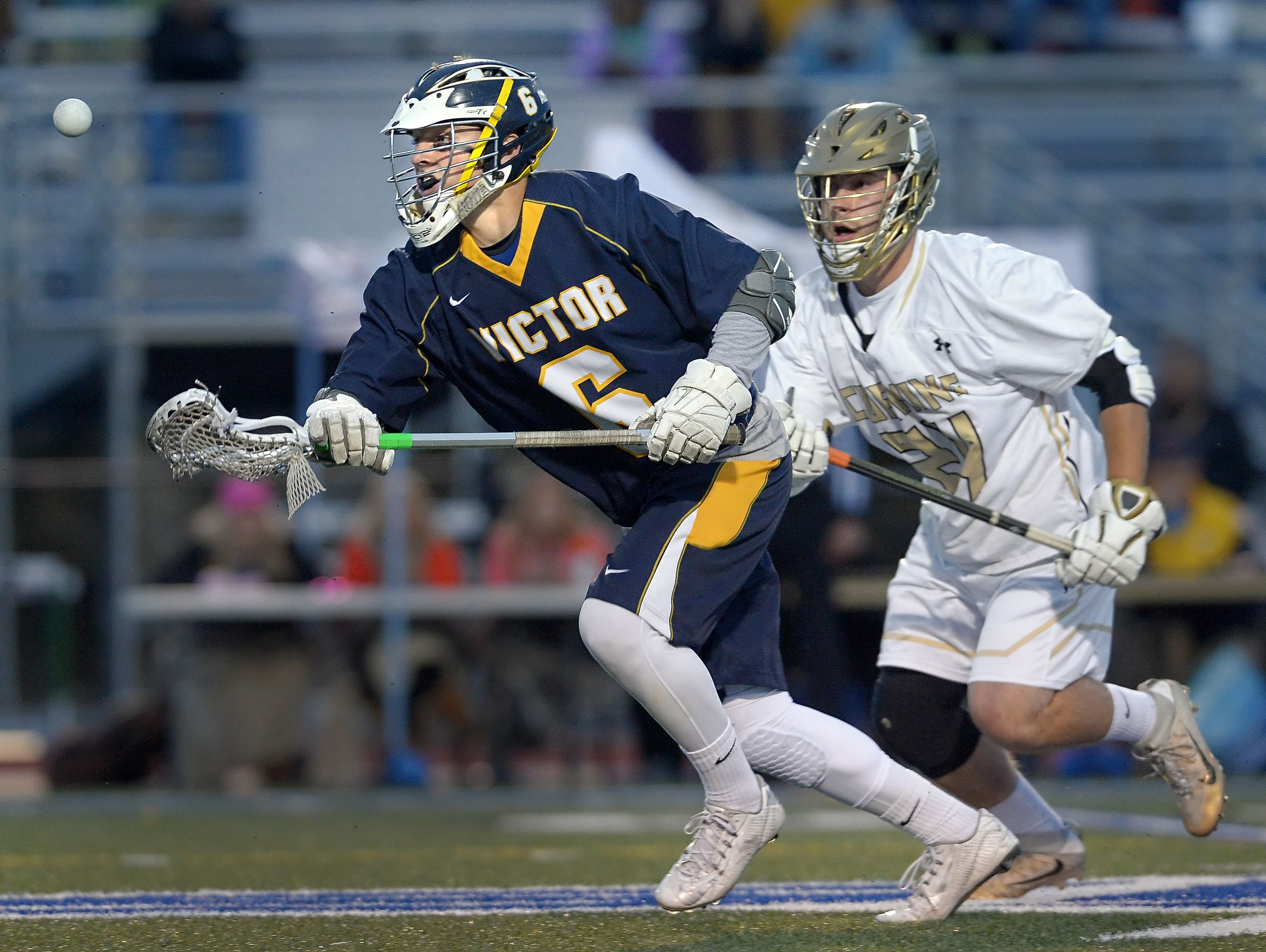Victor's T.D. Ierlan, left, wins a faceoff from Corning's Jake McNaney during the NYSPHSAA Class A Western Semifinal.