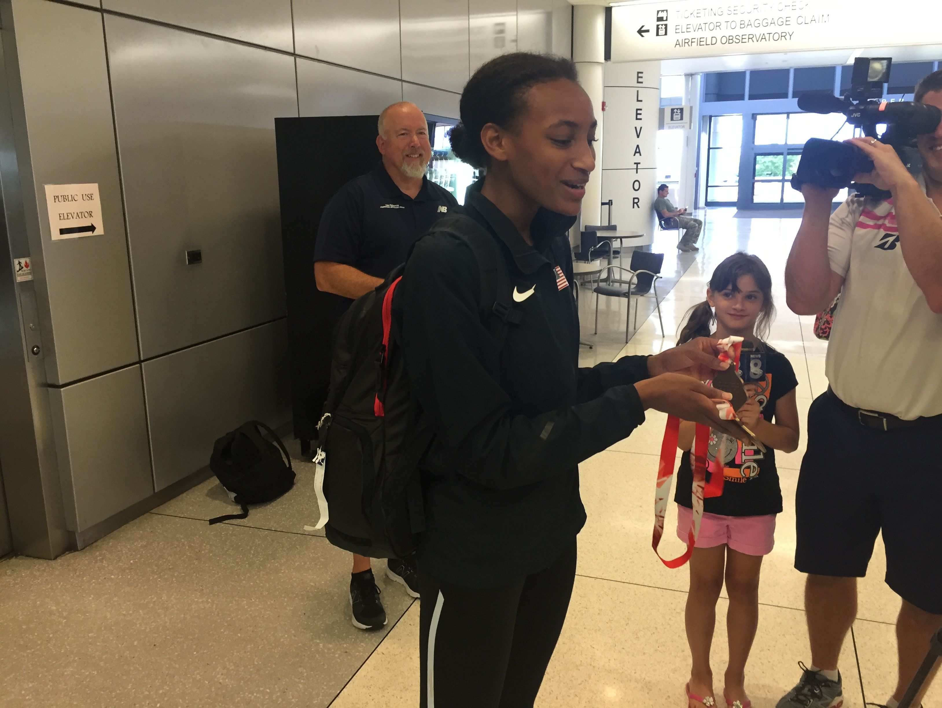 Rush-Henrietta rising senior Sammy Watson was greeted by family, friends, coaches and media at Rochester International Airport on Tuesday. Watson won the IAAF World U20 women's 800-meter final last week in Poland.