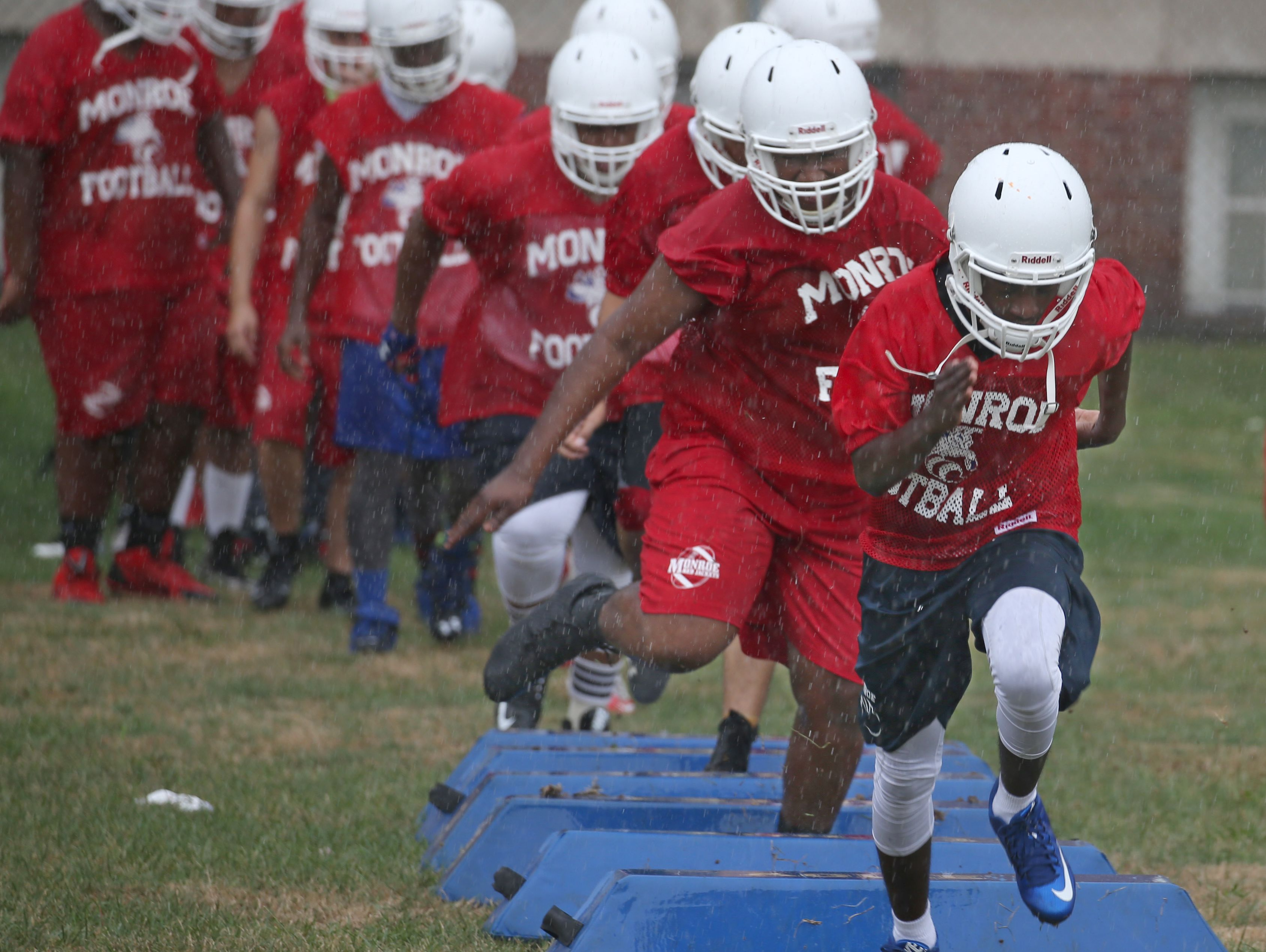 Monroe's John Washington, right, and DeAndre Hill lead the squad as they high-step through agility drills in the rain during varsity football practice at All City High on Ridgeway Avenue in Rochester Tuesday, Aug. 16, 2016.