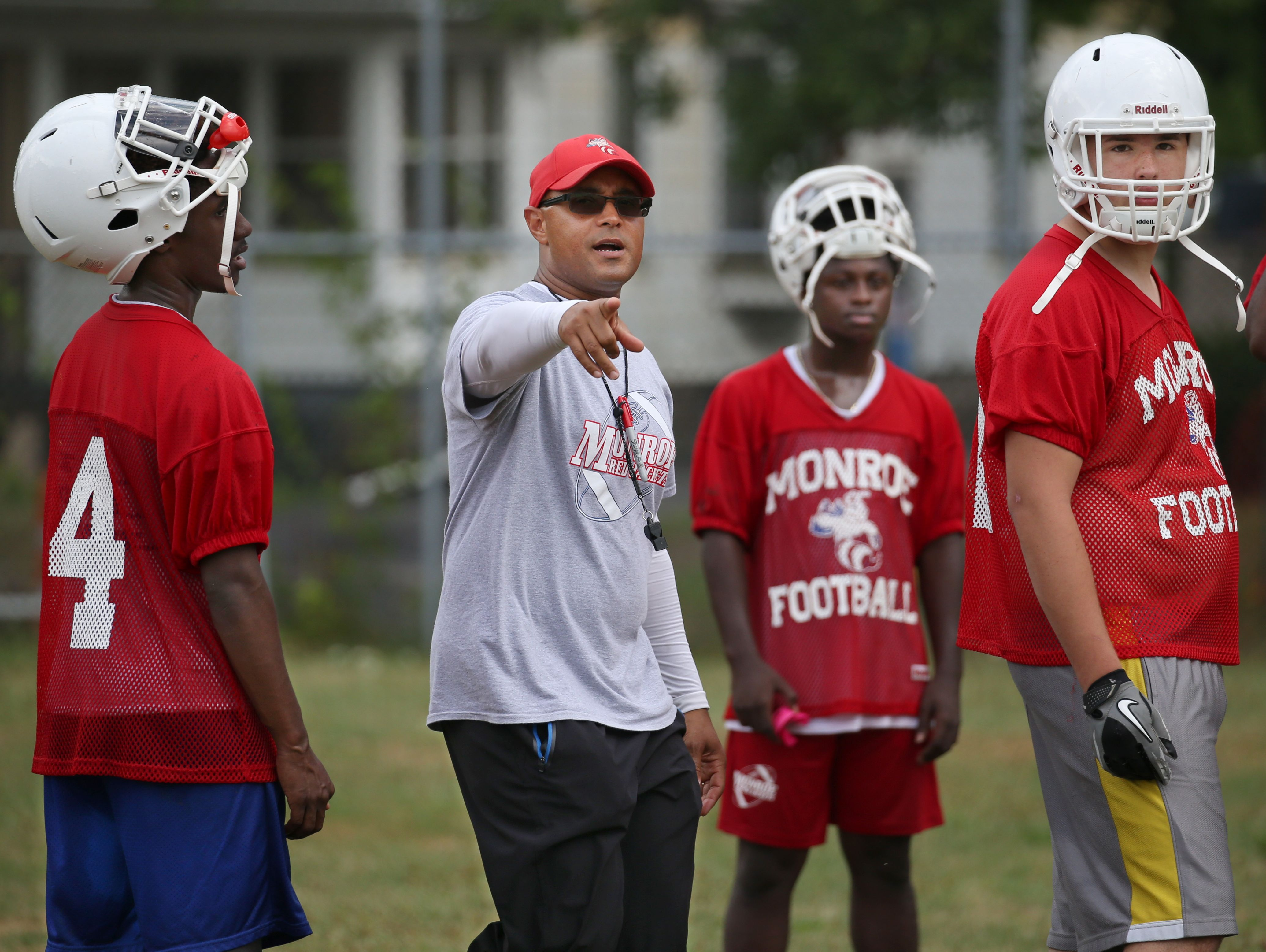 Monroe Head Coach Jason Muhammad leads his squad through punt formations during varsity football practice at All City High on Ridgeway Avenue in Rochester Tuesday, Aug. 16, 2016.