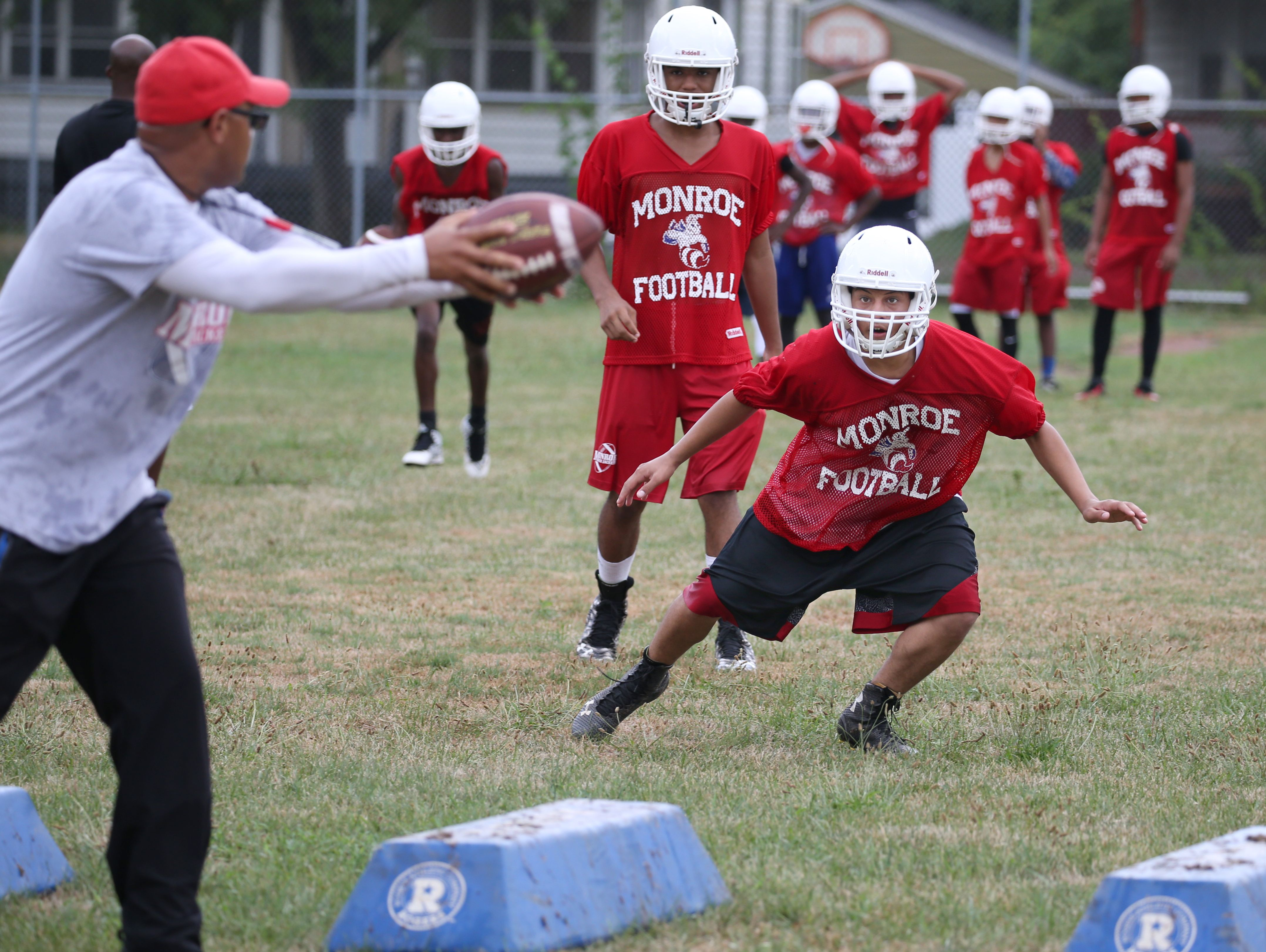 Monroe High linebacker Pablo Alvarez follows the ball as head coach Jason Muhammad simulates a pitch to a running back during linebacker coverage drills during varsity football practice at All City High on Ridgeway Avenue in Rochester Tuesday, Aug. 16, 2016.