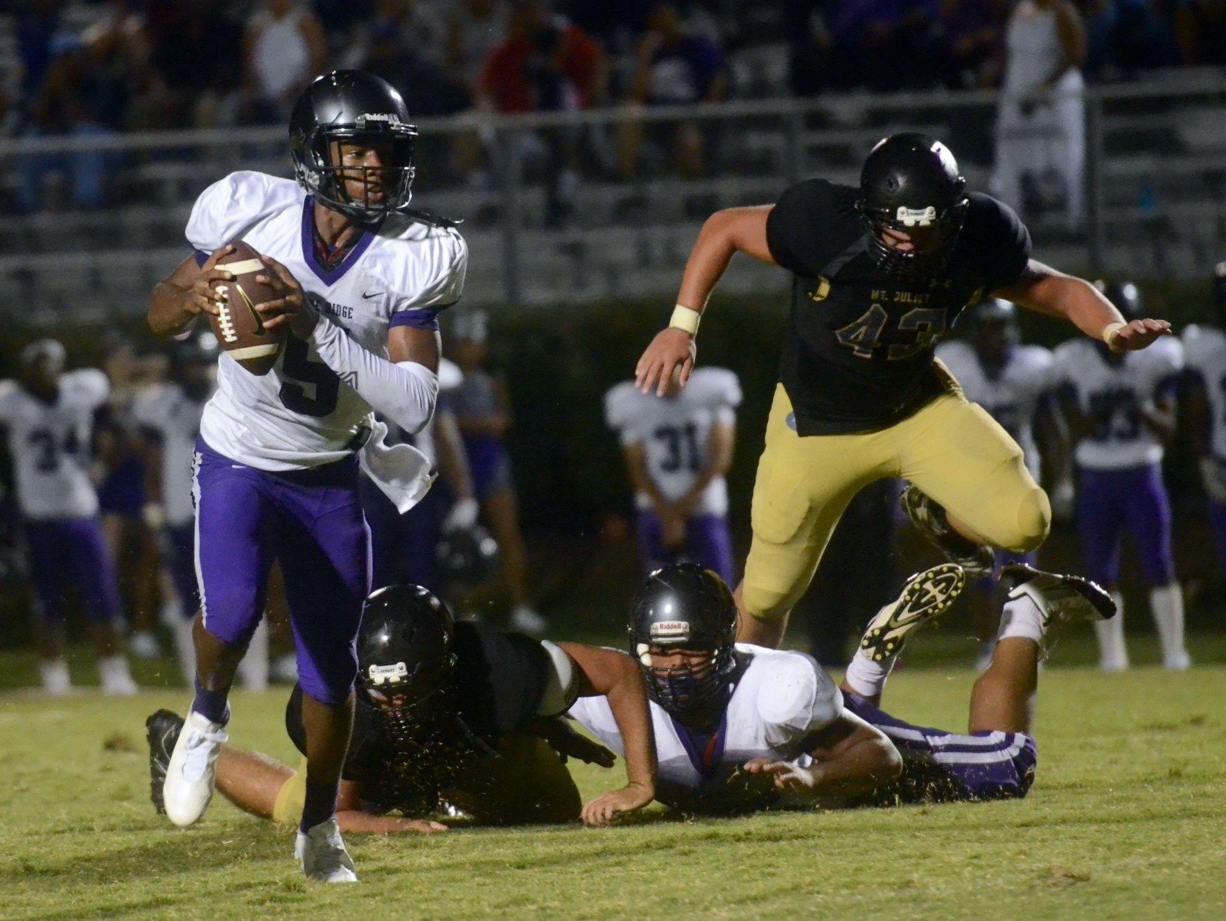 Cane Ridge quarterback D.J. Thorpe eludes the rush as Mt. Juliet's Jacob Shanks (43) pursues during the second quarter of Thursday's game.