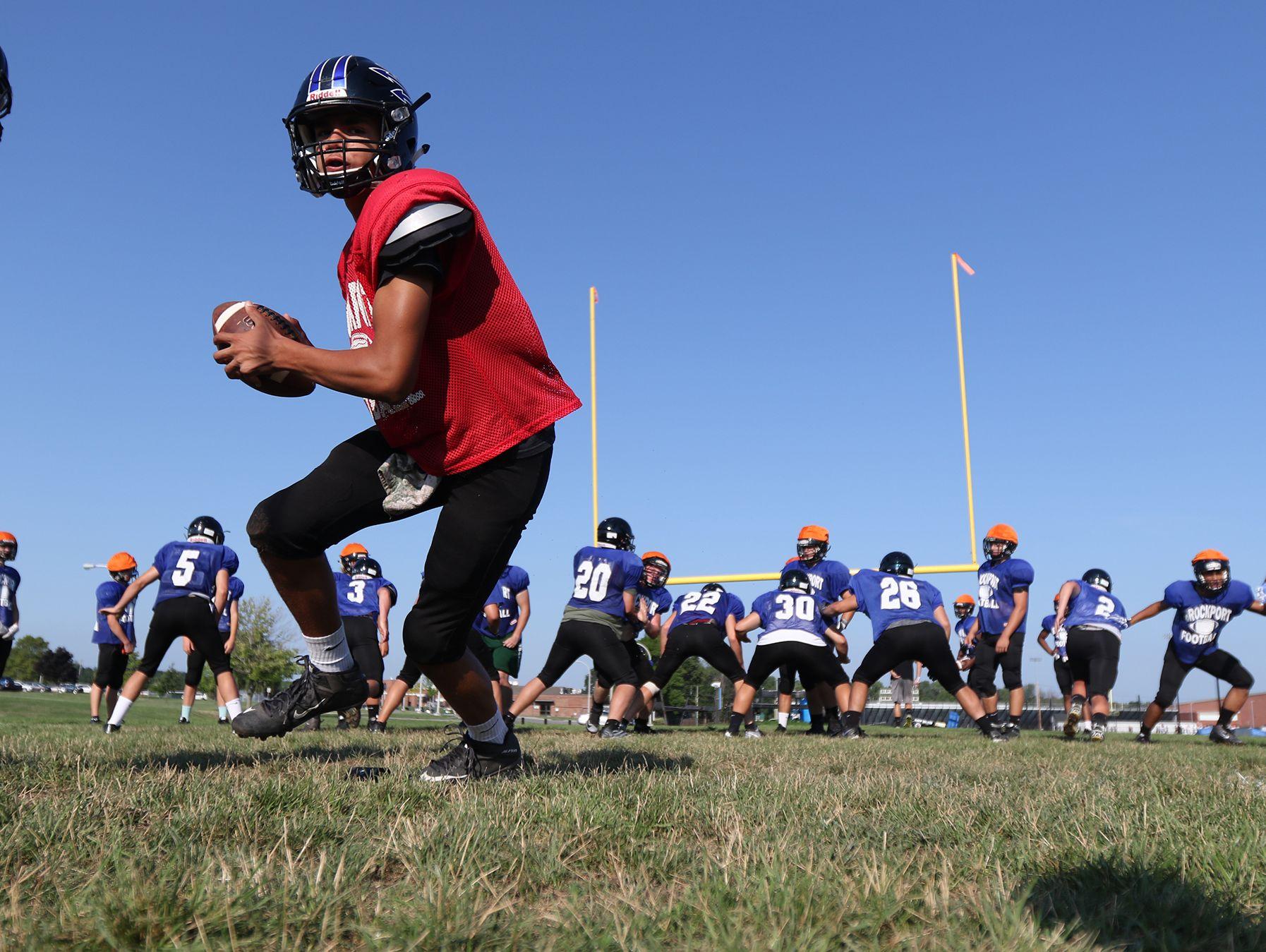 Brockport High School quarterback Ashton Scott rolls back during the team's practice.
