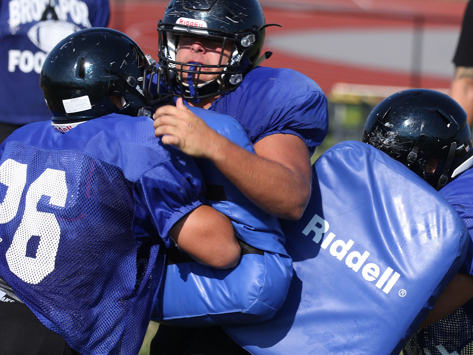 Mike Mattison breaks through a block by Jagger Kachmaryk and Anthony Polizzi.