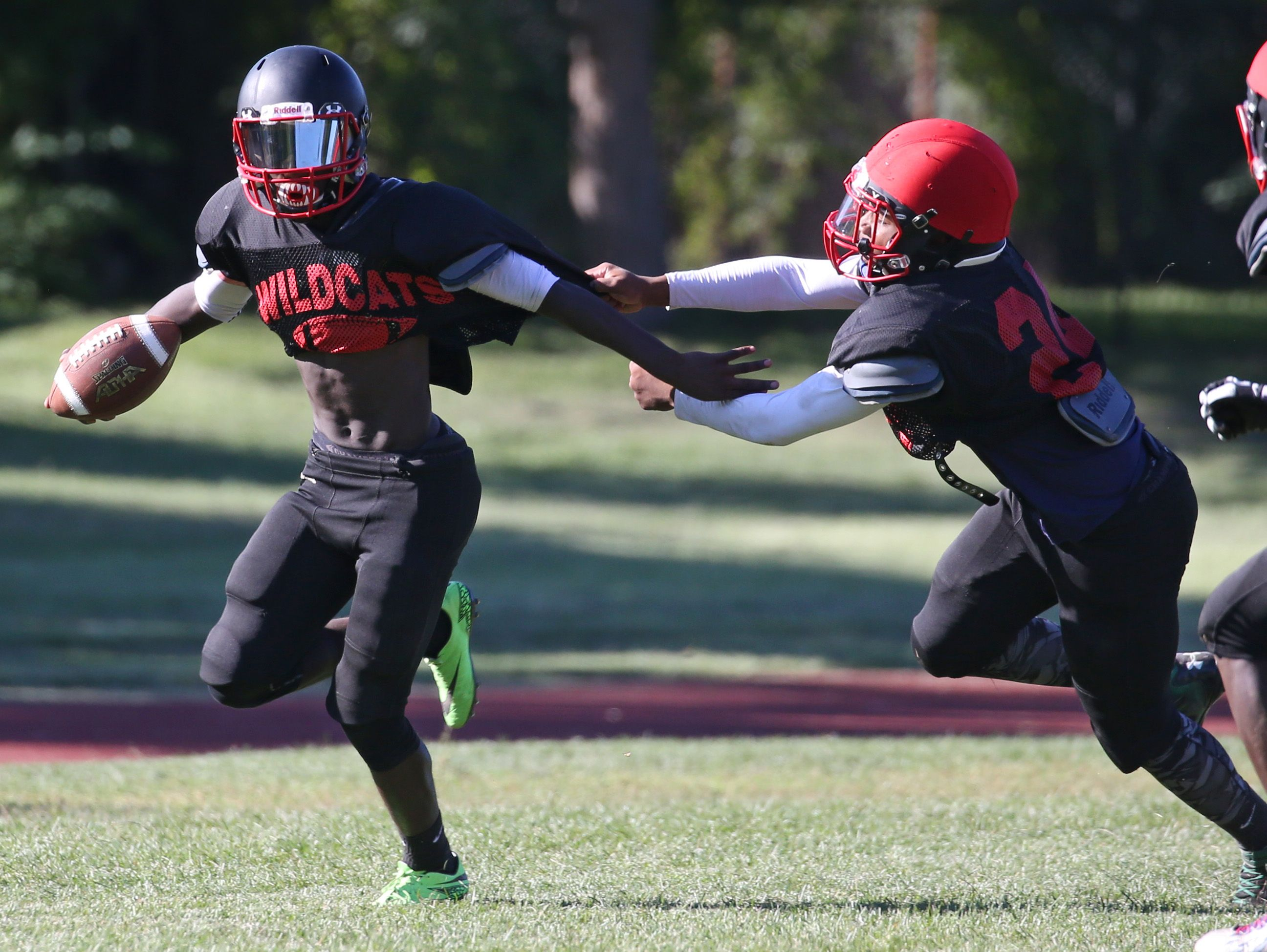 Wilson wide receiver Ricky Gamble, left, sheds tacklers as he races down the sidelines during their practice Monday, Aug. 29, 2016 in Rochester.