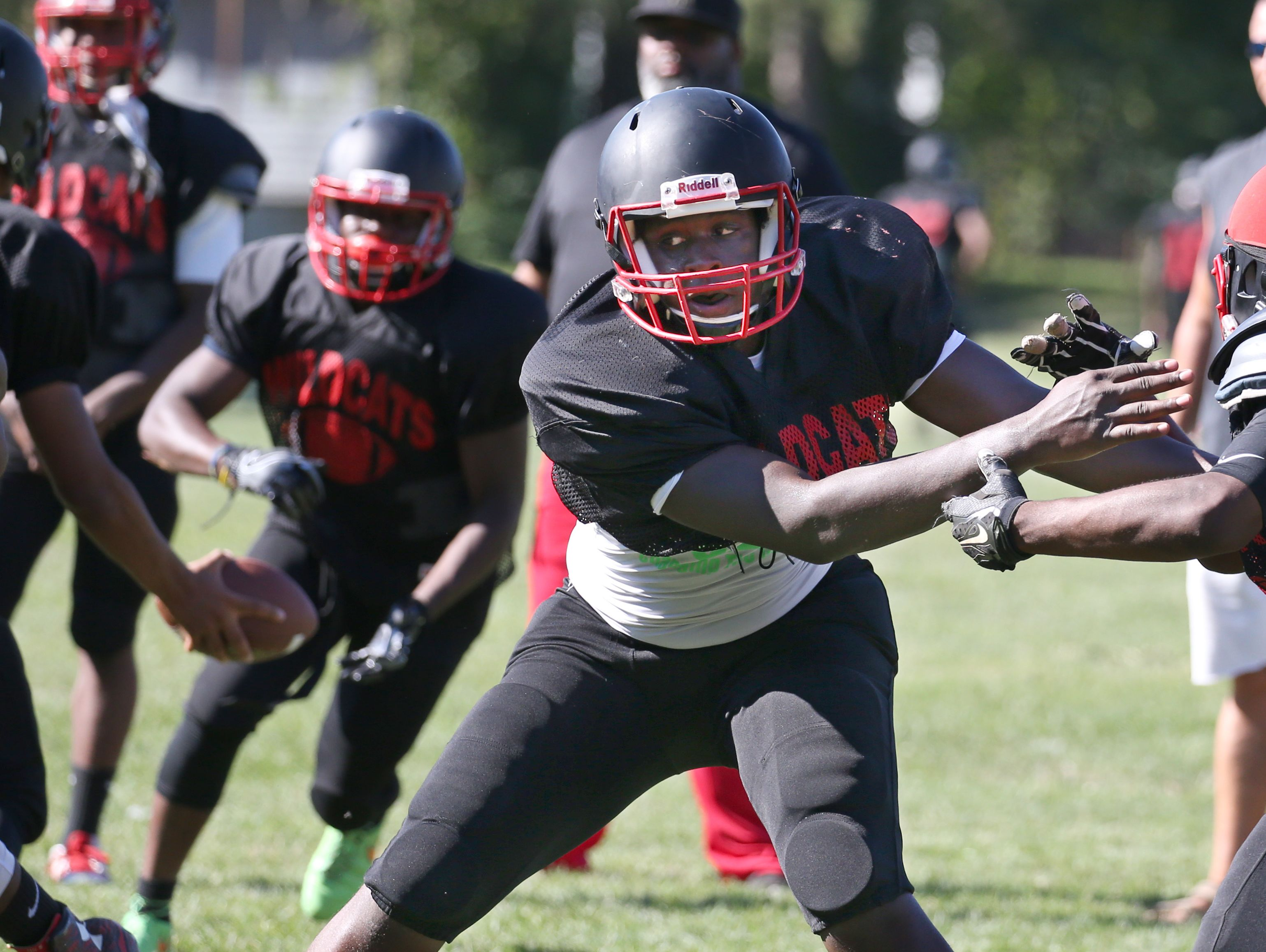 Wilson lineman Jamal McCullogh, second from right, throws his block away as he protects quarterback James Cotton, back left, who hands the ball off to running back Earl English during their practice Monday, Aug. 29, 2016 in Rochester.