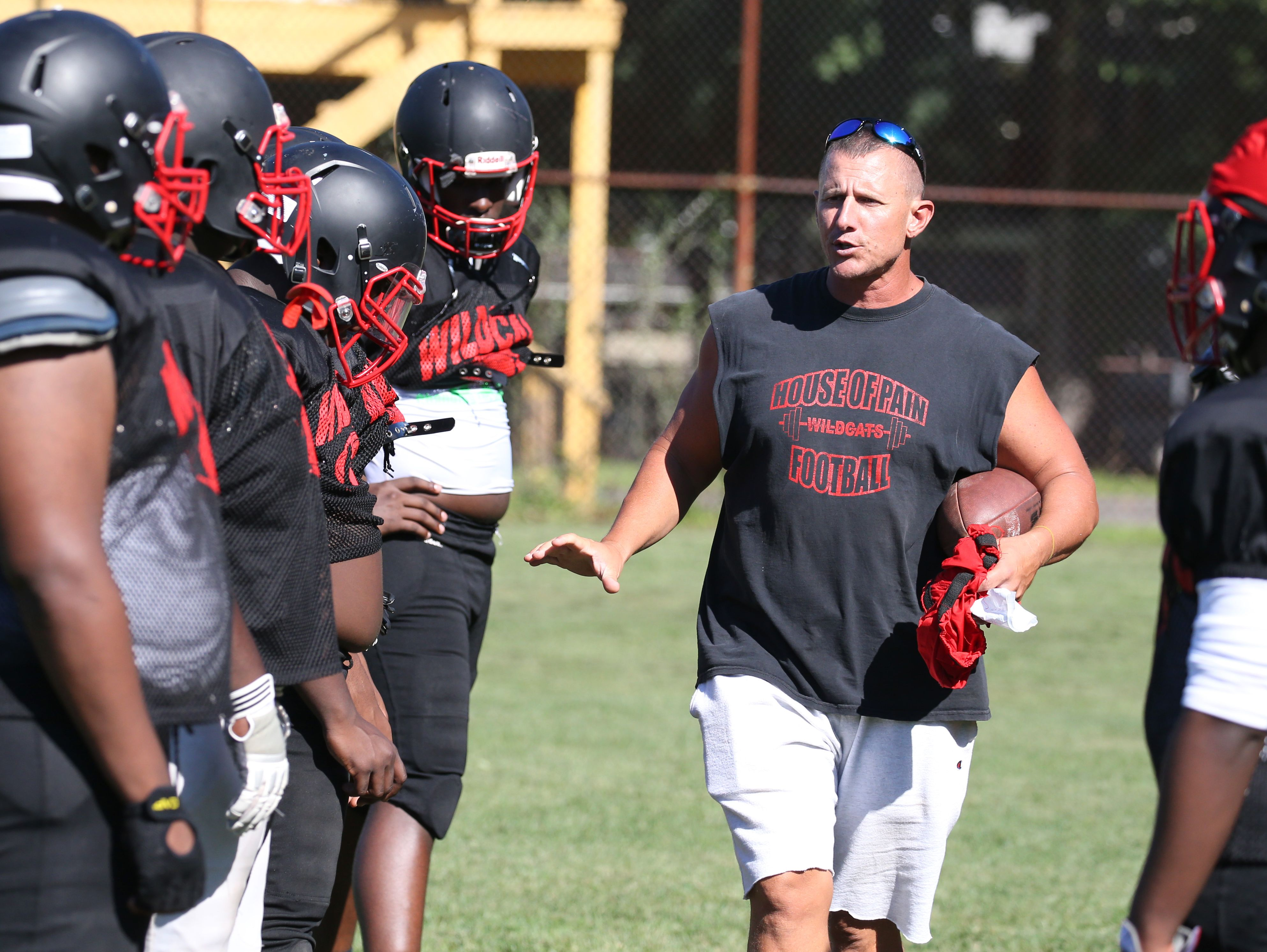 Wilson head coach Greg Mortier works with his offensive line during their practice Monday, Aug. 29, 2016 in Rochester.