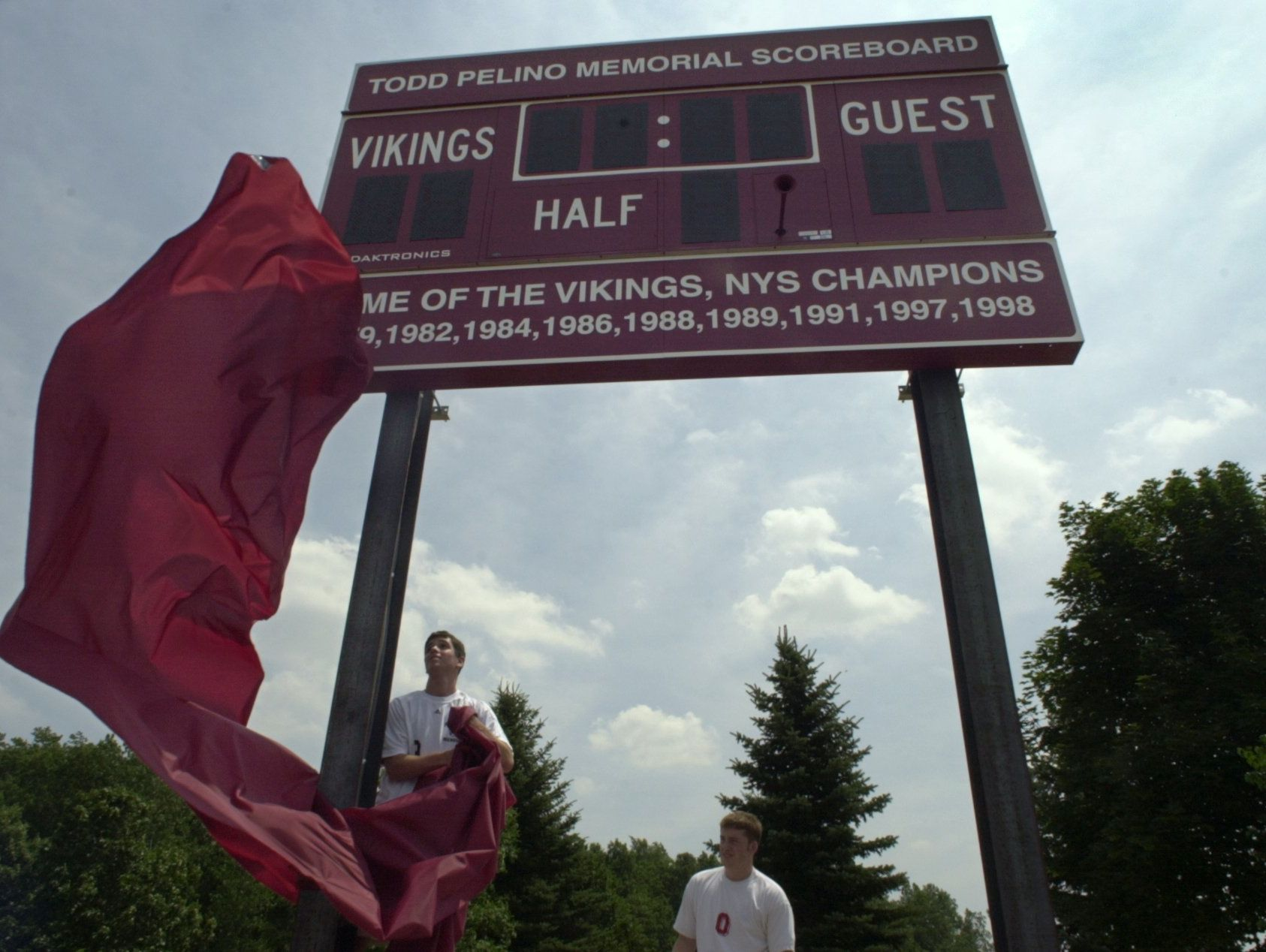 Then-players Angelo Suozzi, left, and James McKenna unveiled new scoreboard at Pittsford Mendon when it was dedicated in July 2002 in honor of Todd Pelino, a former Vikings player who was killed during the World Trade Center attacks on Sept. 11, 2001. The scoreboard at the school's new soccer field, which opened this month, also features the name of Pelino, a 1985 graduate who was 34 at the time of his death.