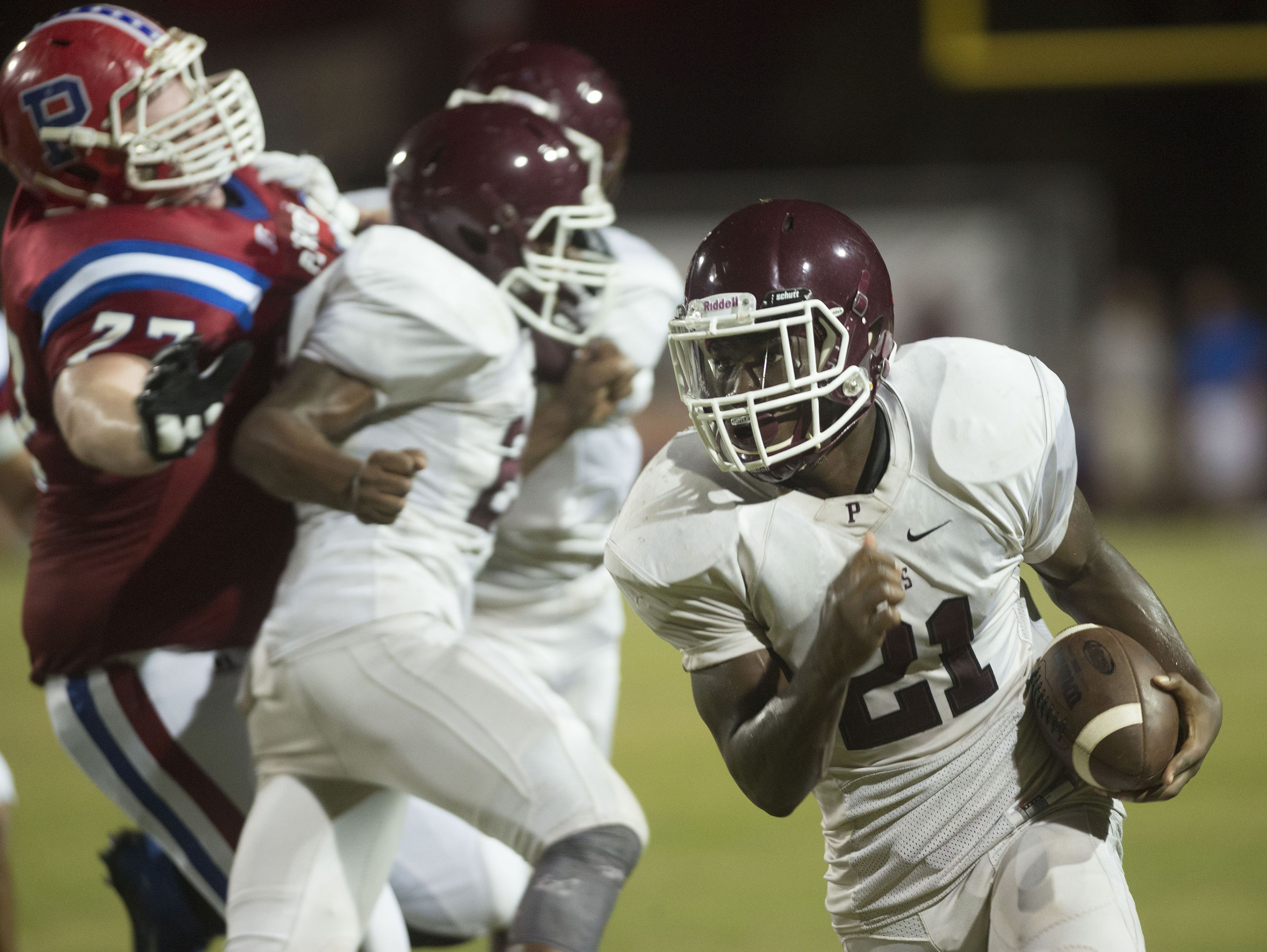 Pensacola High School running back Kenneth Hamilton, (No. 21), turns up field for extra yards thanks to the blocking of his teammates during Friday night's game against Pace High.