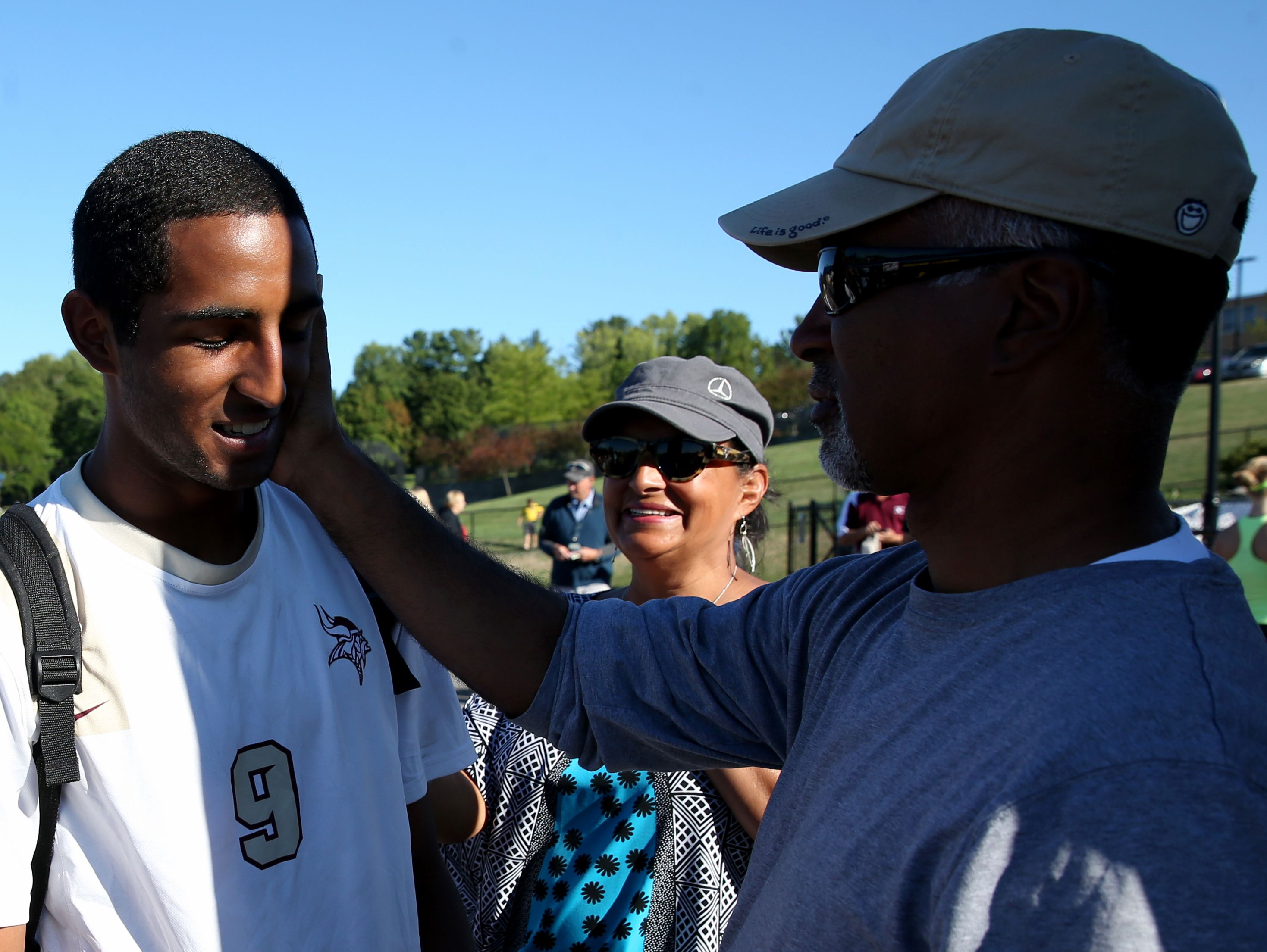 Adrian Padilla's father, Donald, touches his cheek after the Pittsford Mendon soccer team defeated Aquinas as Adrian's mother, Maria, center, looks on. Donald Padilla, now a retired state trooper, worked for a couple months at Ground Zero during the cleanup following the attacks.