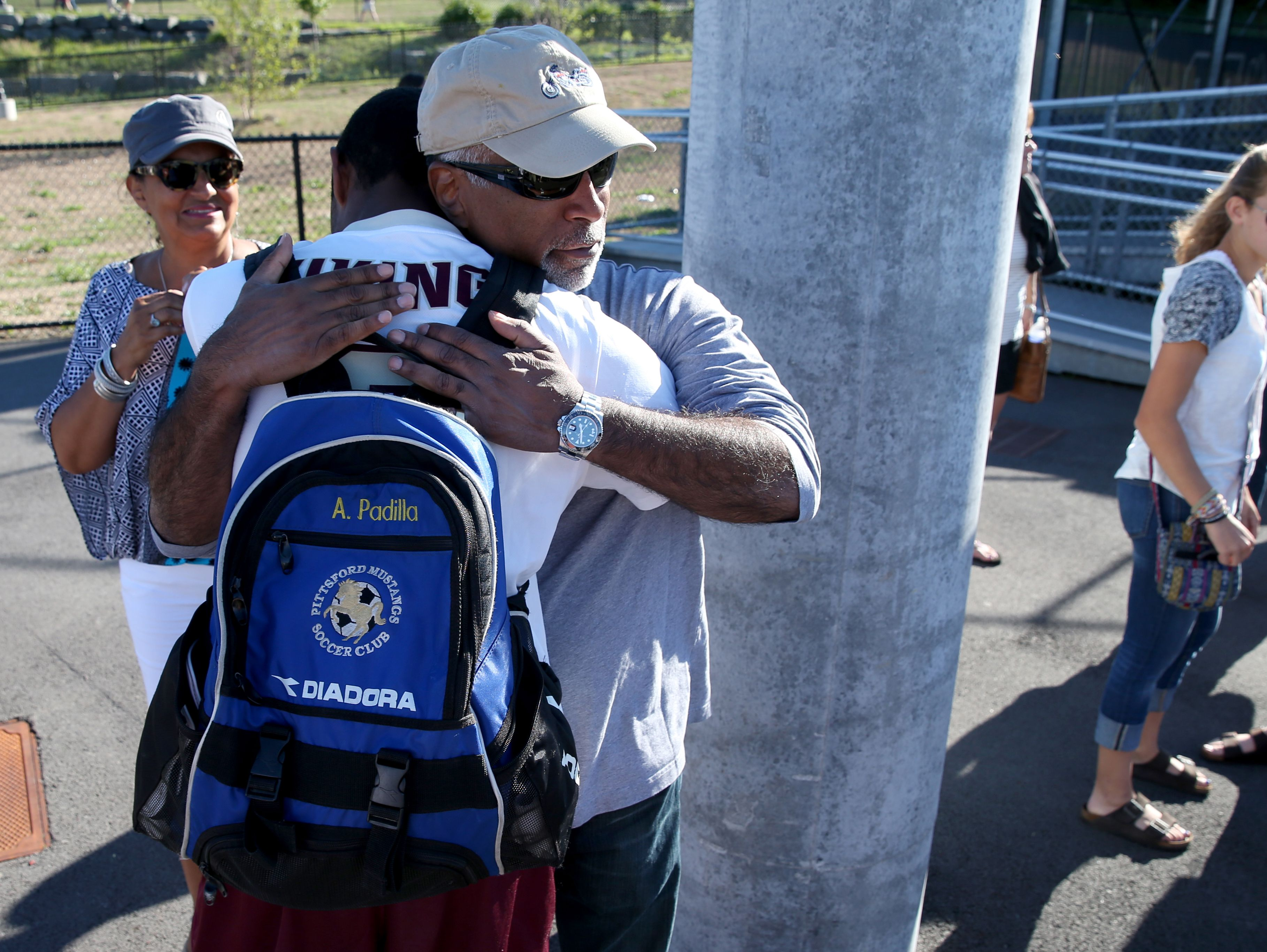 Adrian Padilla gets a hug from his father, Donald, after the Pittsford Mendon boys soccer team defeated Aquinas.