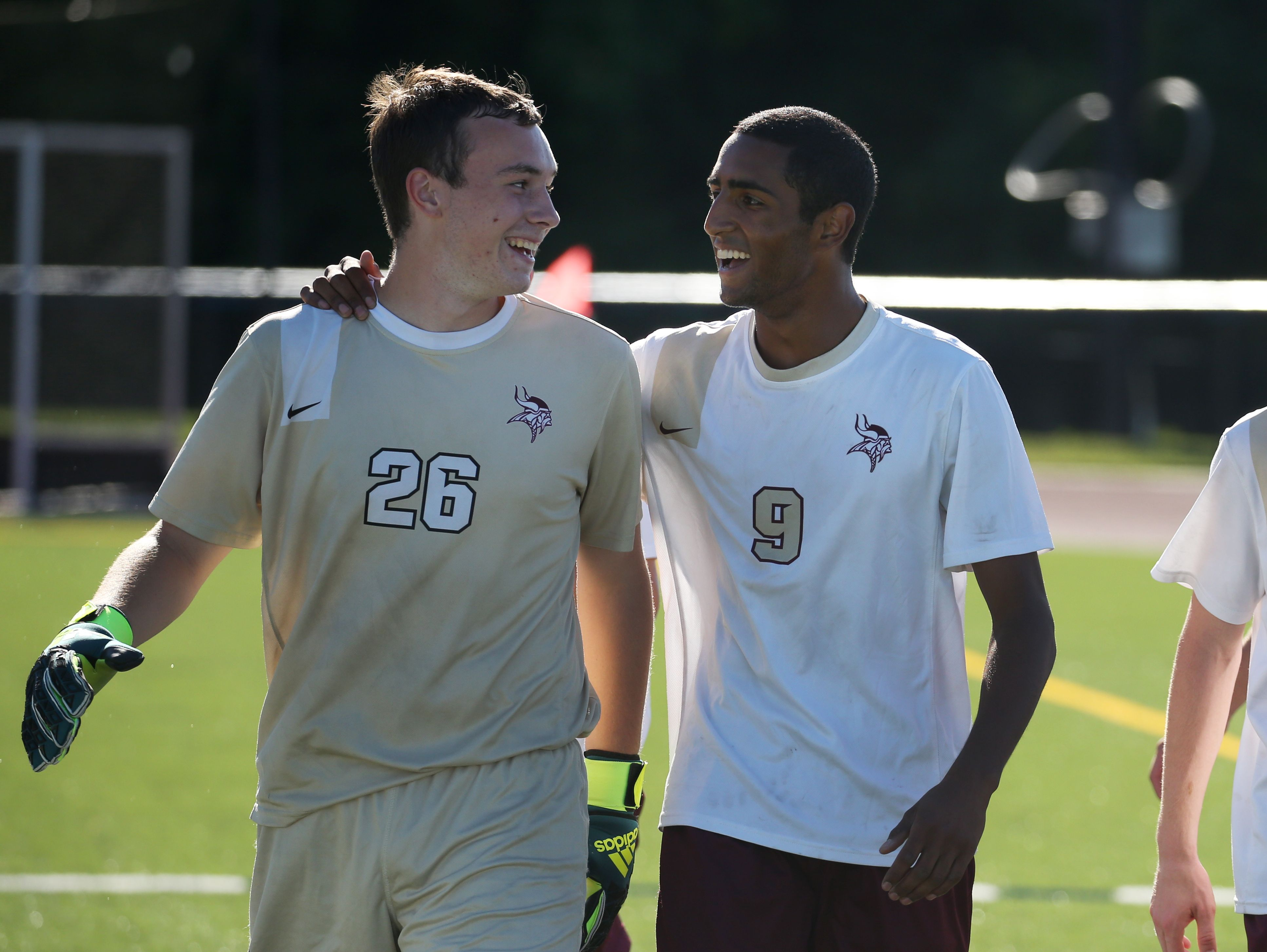 """Adrian Padilla (9) and Winston Bennett (26) of Pittsford Mendon celebrate their season-opening win against Aquinas. His team's vote for him to wear No. 9 """"means these people that I grew up with trust me to lead them,"""" Padilla says."""