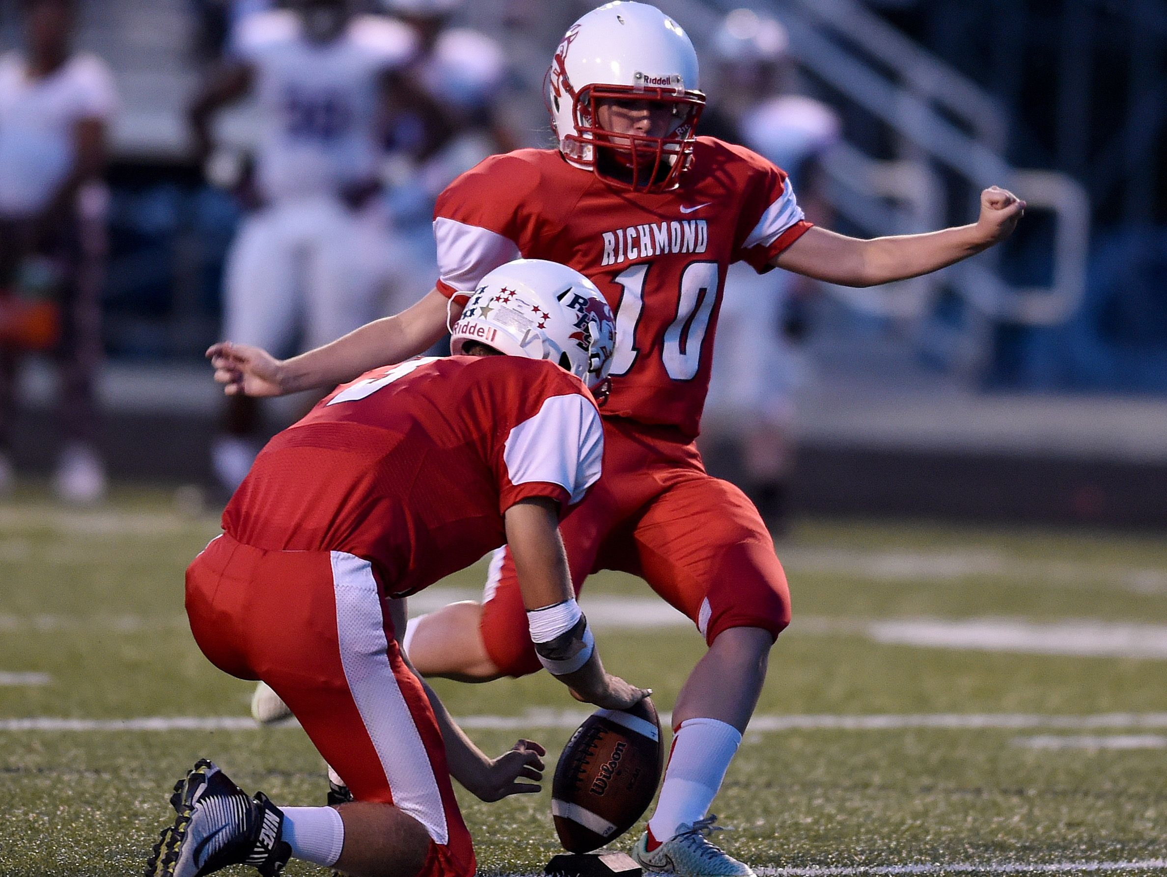 Richmond's Alec Snedigar holds the ball as Alexis Shiplett kicks against Muncie Central Friday, Sept. 9, 2016, during a football game on Lyboult Field.