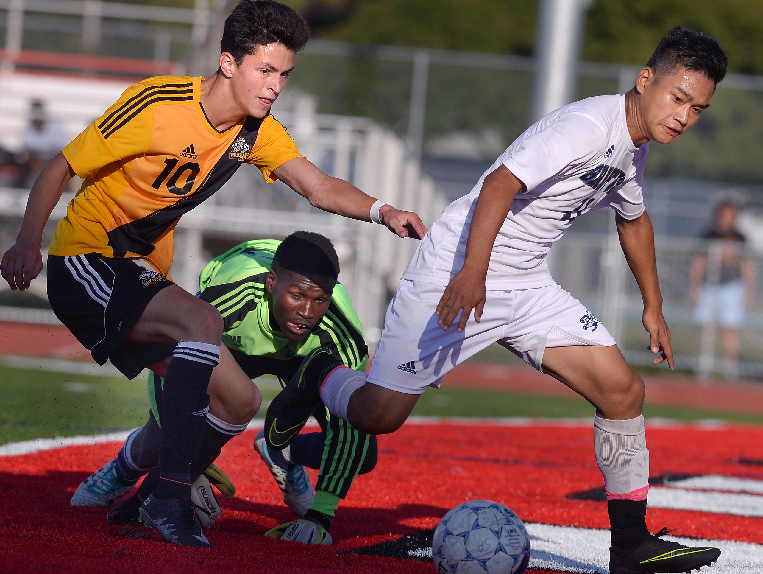 McQuaid's Dan Malloy, left, chases a loose ball with World of Inquiry goalie Jean Sindayihebura and Wah Gay Doh during a game on Sept. 21.