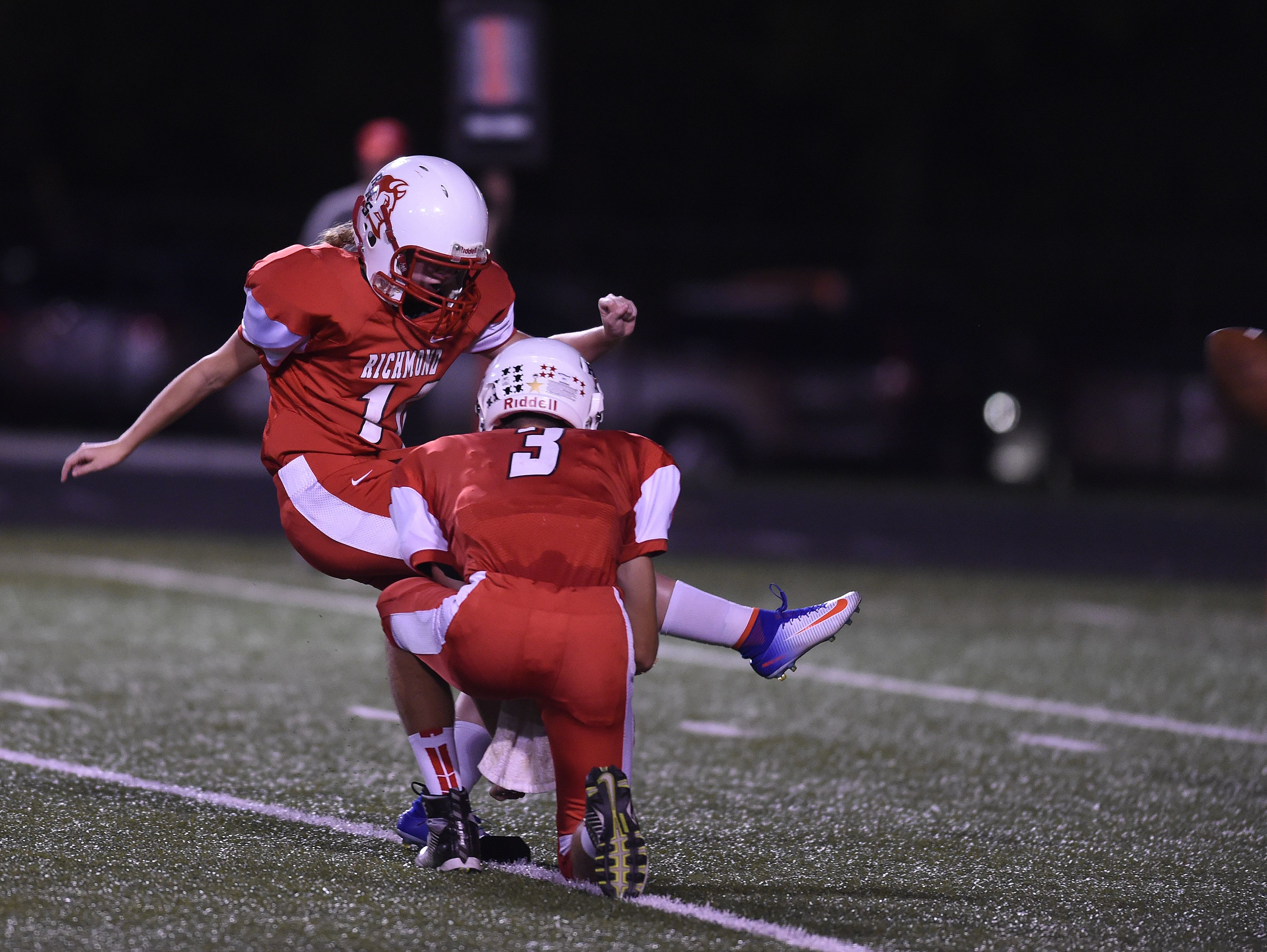 Richmond's Alec Snedigar holds the ball as Alexis Shiplett kicks an extra point against Logansport Friday, Sept. 23, 2016 during a football game on Lyboult Field.