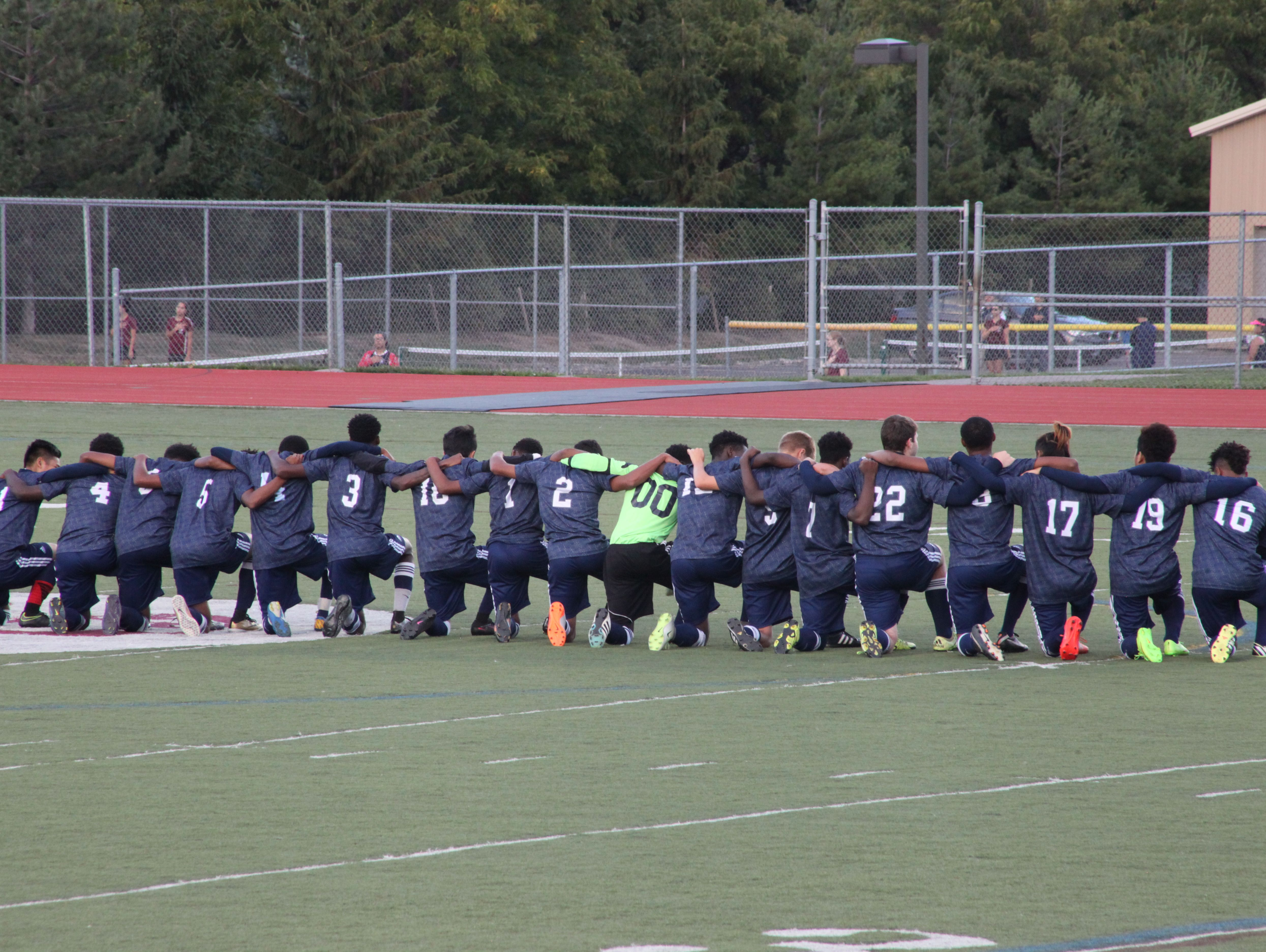 All 18 players for the World of Inquiry boys soccer team knelt during the anthem before Tuesday's match at Aquinas Institute.