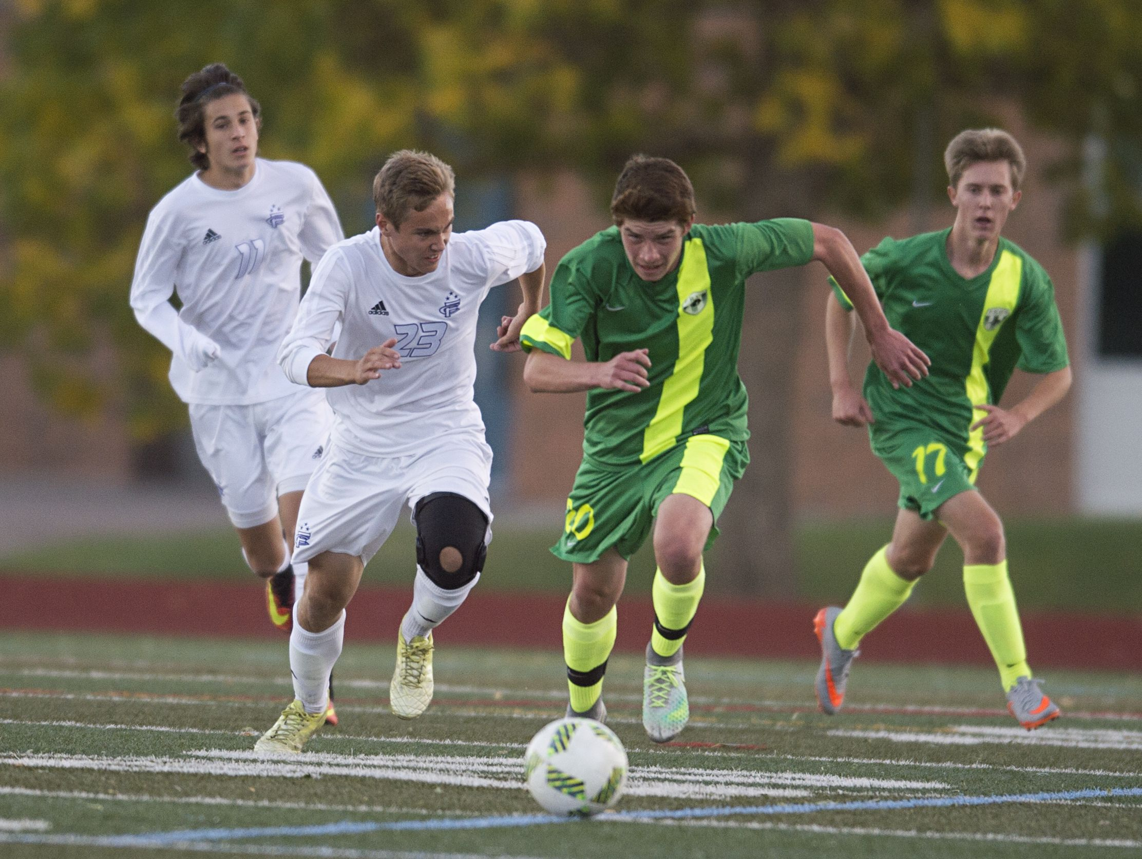 Alec Fronapfel of Fort Collins and Tyler Hause of Fossil Ridge High School race towards the ball during a game at French Field Tuesday, October 4, 2016.