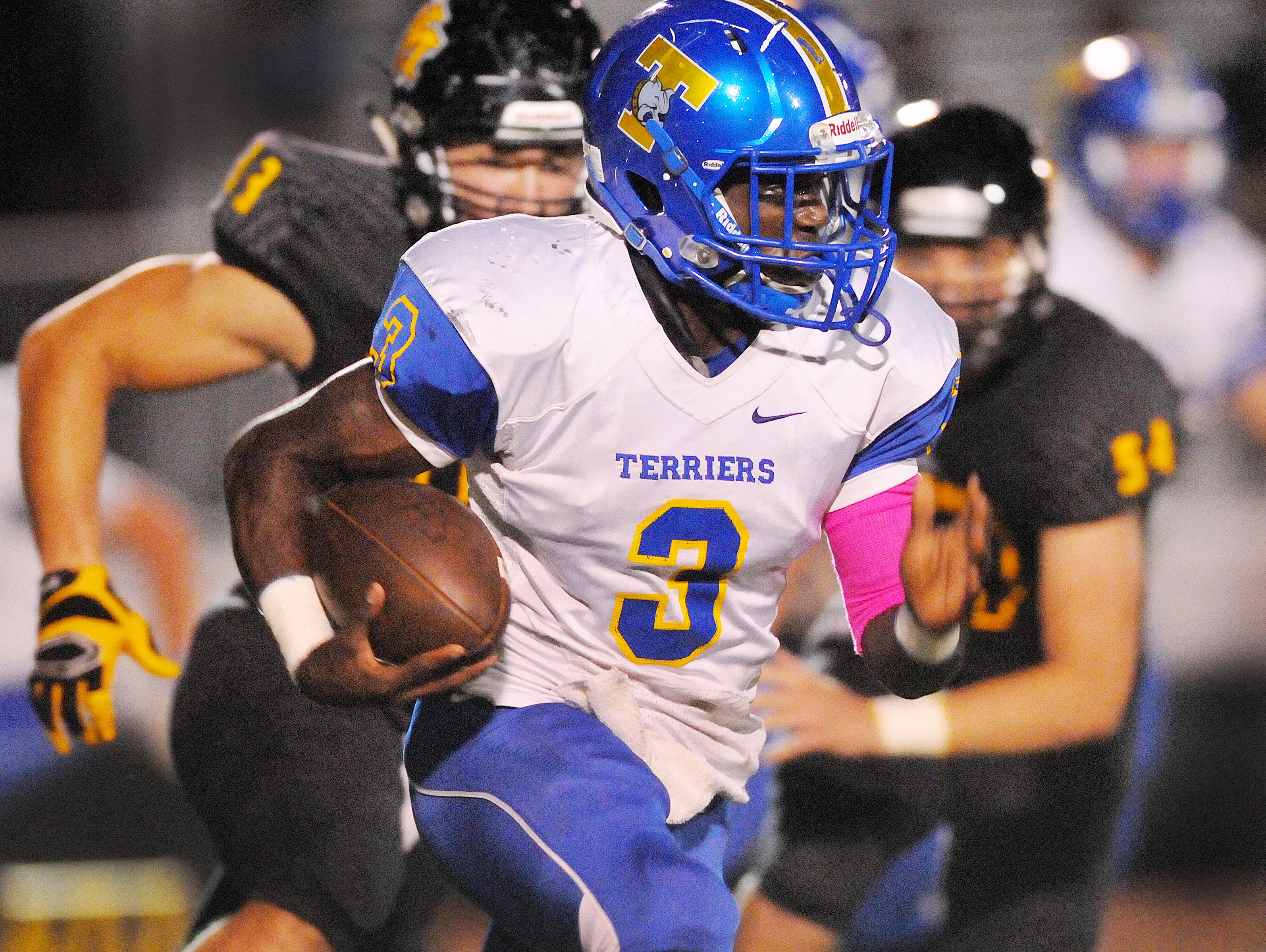 Titusville High's Dontavious Marcus turns the corner around a host of Merritt Island High defenders during a game this season.