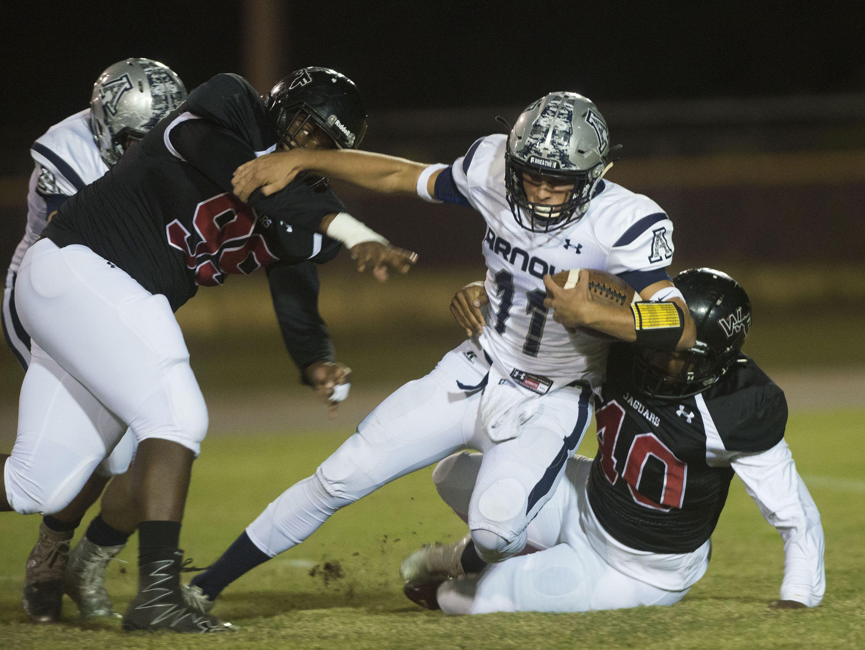 West Florida High School's Adarius McWilliams, (No.99), and Vidal Scott, (No. 40) sacks Arnold High quarterback Cade Ledman, (No. 11) during Friday night's District 1 5-A game.