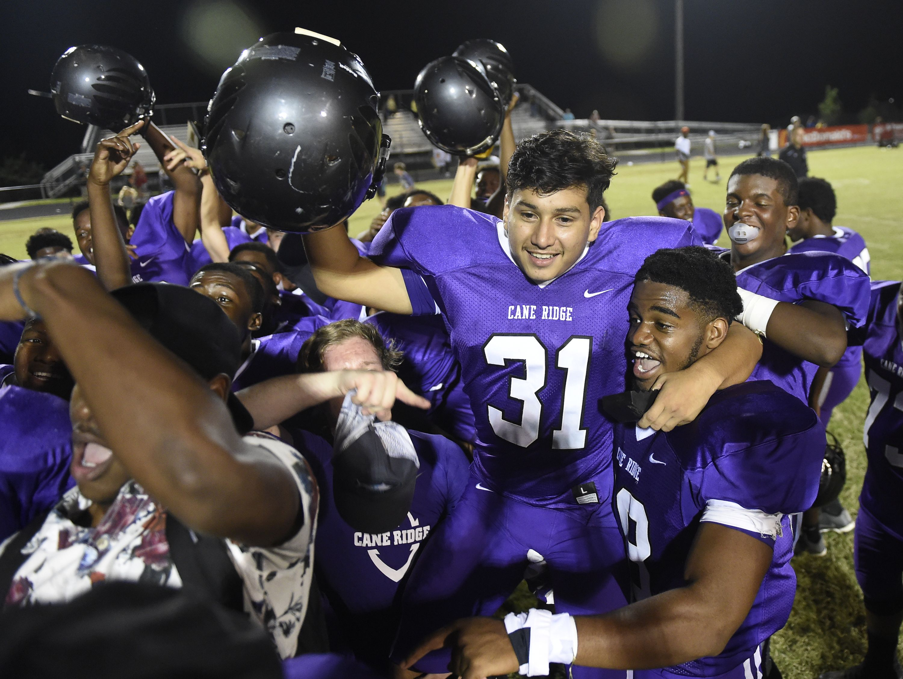 Cane Ridge kicker Carlos Velasquez (31) is lifted onto the shoulders of his teammates after he kicked the game-winning extra point in OT. Cane Ridge kicker Carlos Velasquez, 31, is lifted onto the shoulders of his teammates after he kicked the game winner to top Hendersonville 47-46 in overtime on Friday, September 2, 2016.