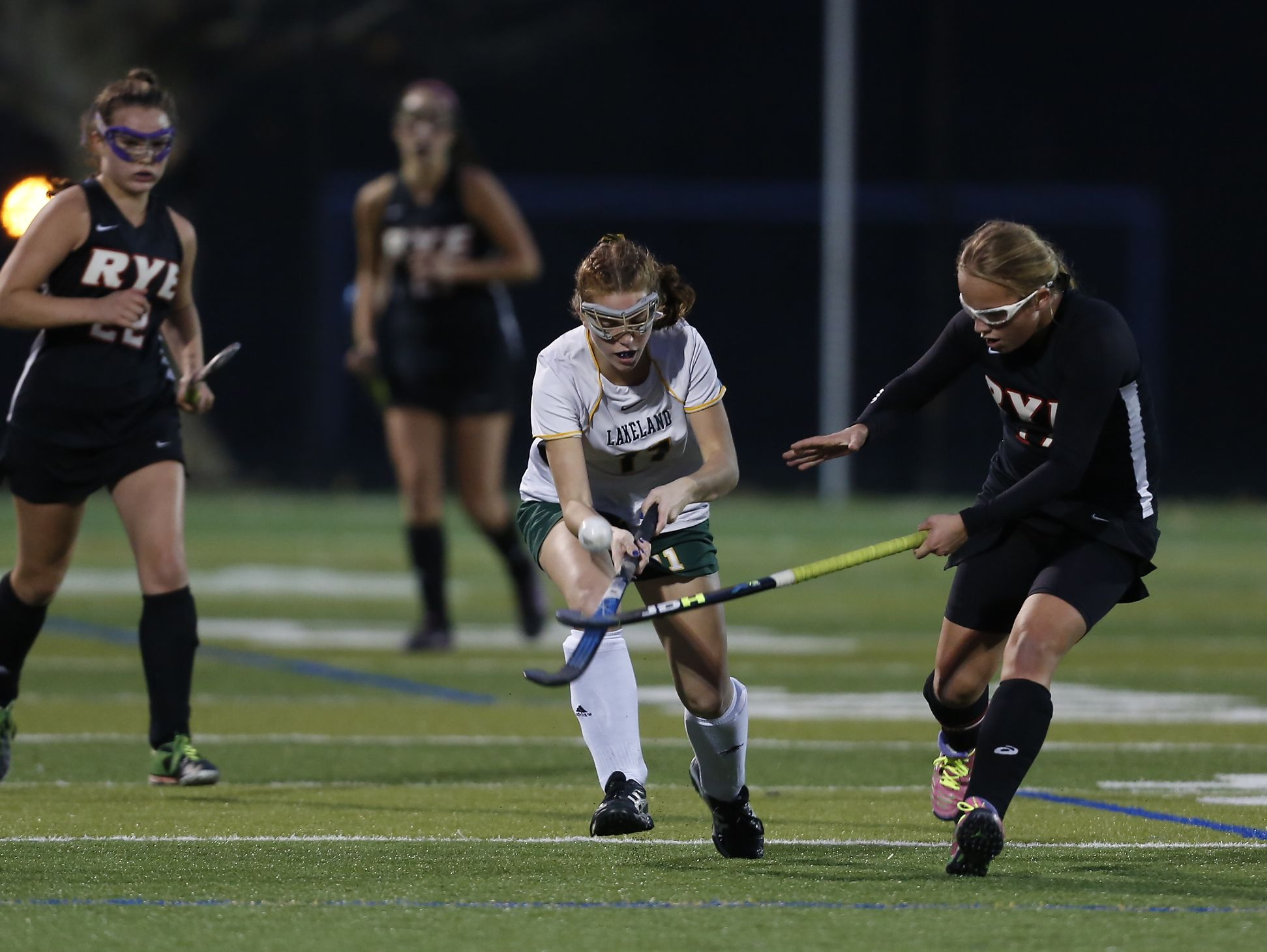 Lakeland's Julianna Cappello (11) flips the ball past a Rye defender during their 4-1 win in the Class B field hockey section finals at Brewster High School on Tuesday, November 1, 2016.