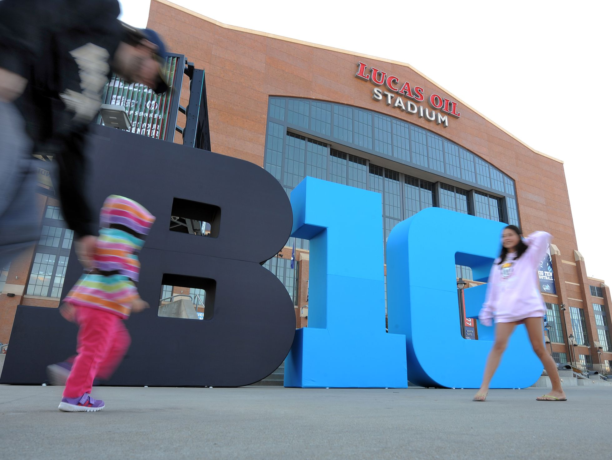 Big Ten football fans walk by the Big Ten logo out front of Lucas Oil Stadium Friday afternoon in preparation for this the Big Ten football championship game Saturday evening. The Big Ten Fan Fest will also be open Saturday from 10 a.m. to 8 p.m. Matt Kryger / The Star