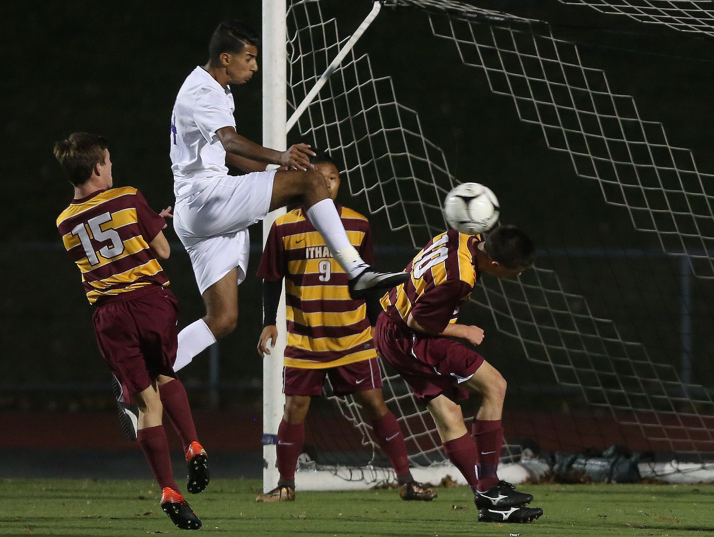 New Rochelle's (14) kicks the ball away from an Ithaca defender during the boys soccer regional semifinal at Lakeland High School in Shrub Oak Nov. 2, 2016.