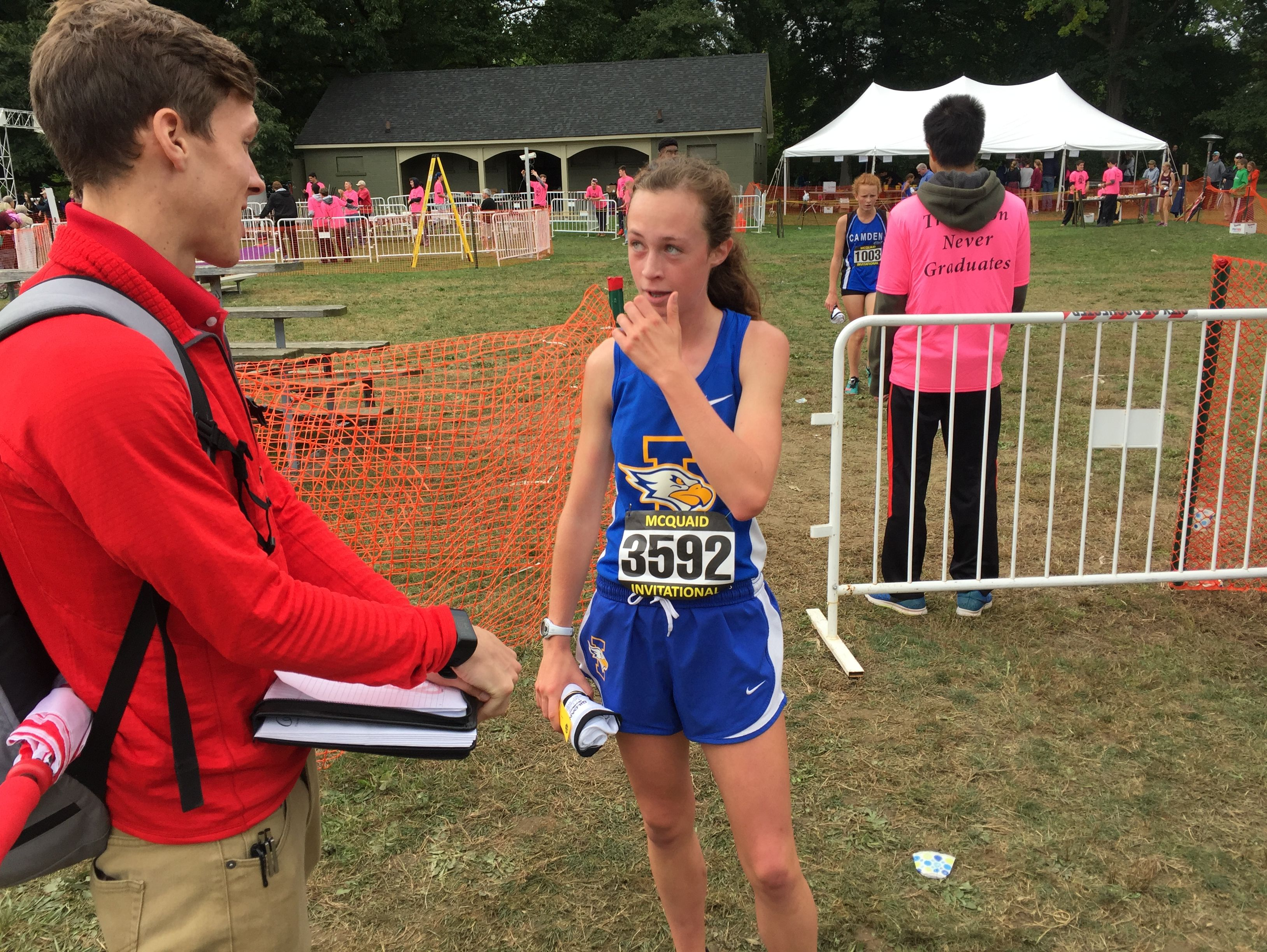 Irondequoit junior Madeleine Shellard with a college coach, after her first-place finish in an unseeded race during the 2016 McQuaid Invitational